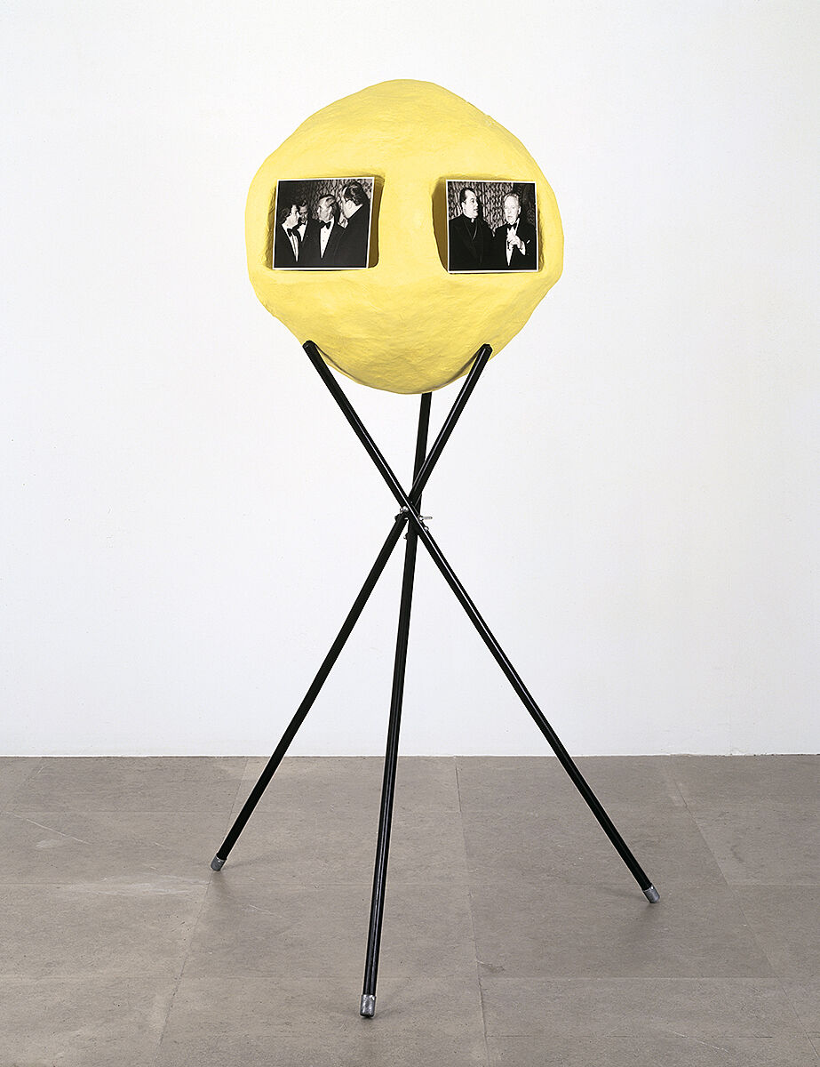 A sculpture with a yellow sphere, black and white photos, and a black tripod-like structure.