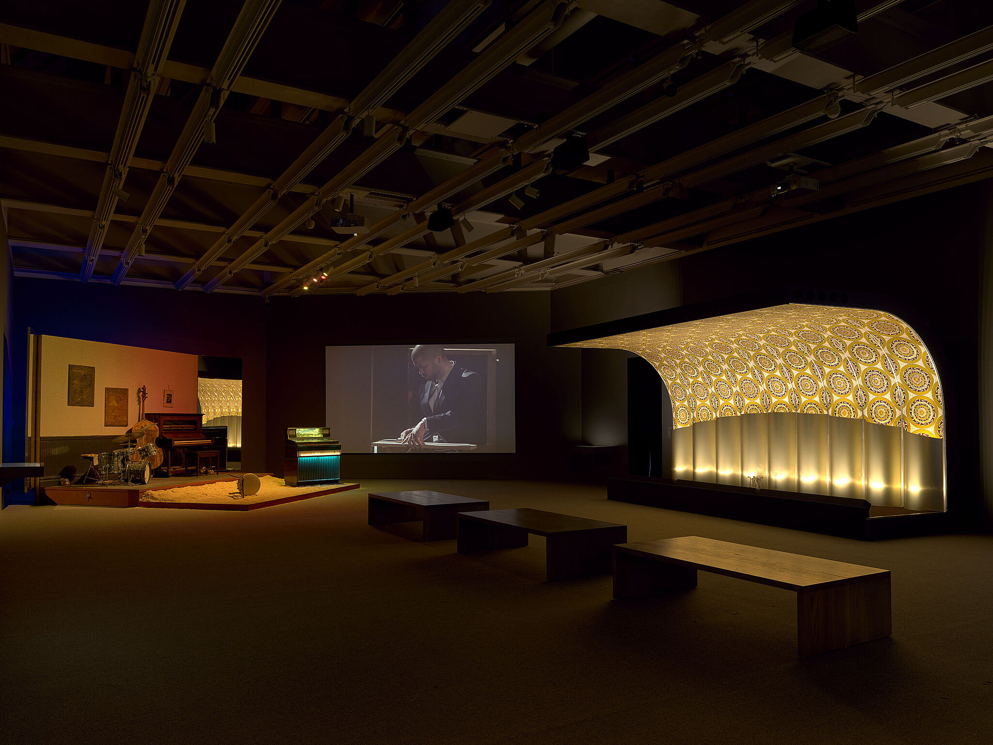 An image of a gallery with three stages and various musical instruments and video projections.