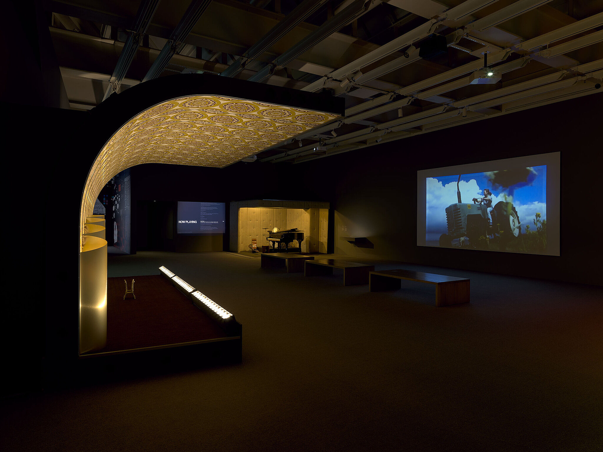 An image of the Whitney galleries with various video projections, stages, and musical instruments