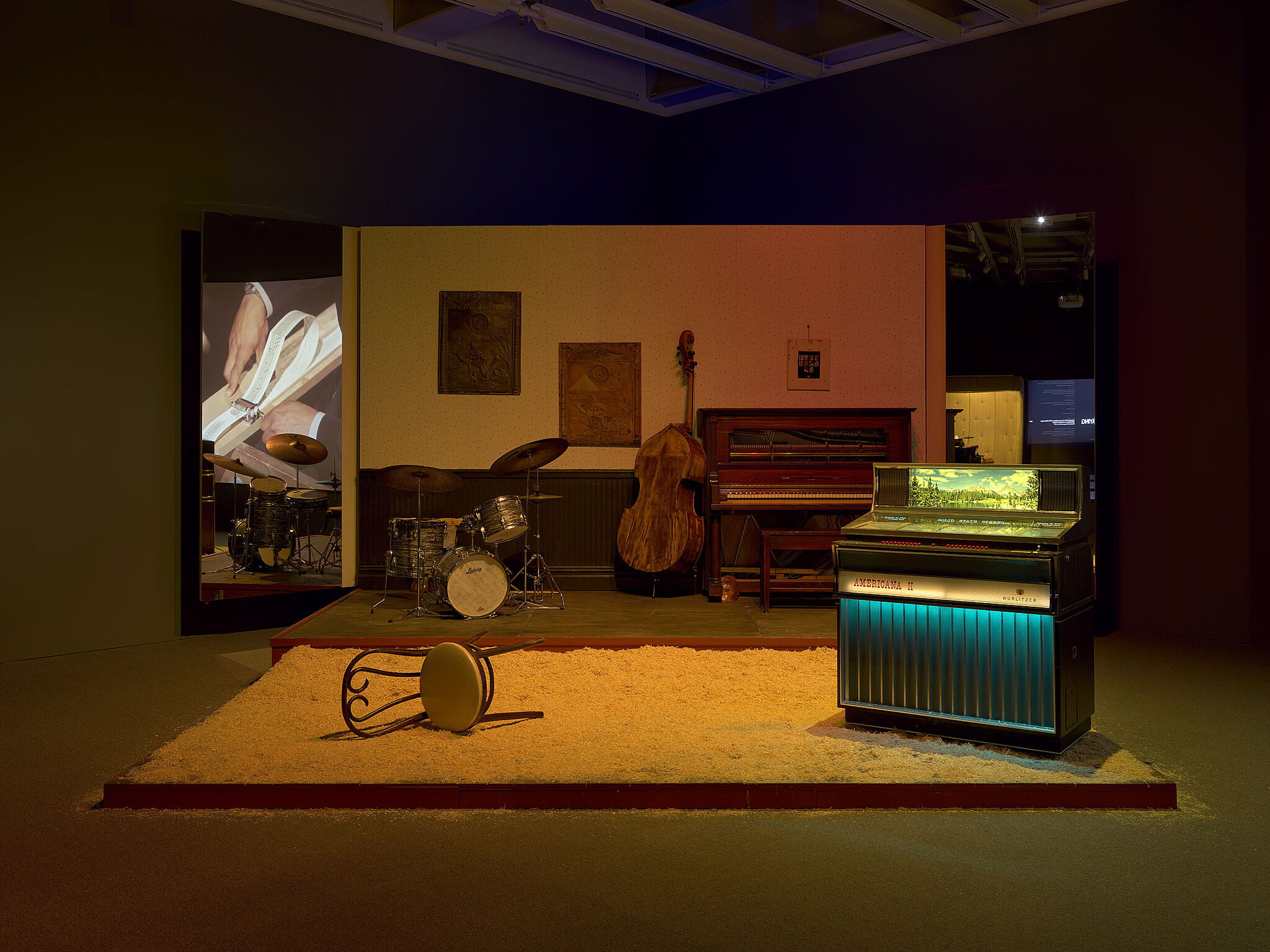 A stage with various musical instruments, a jukebox, and an overturned chair