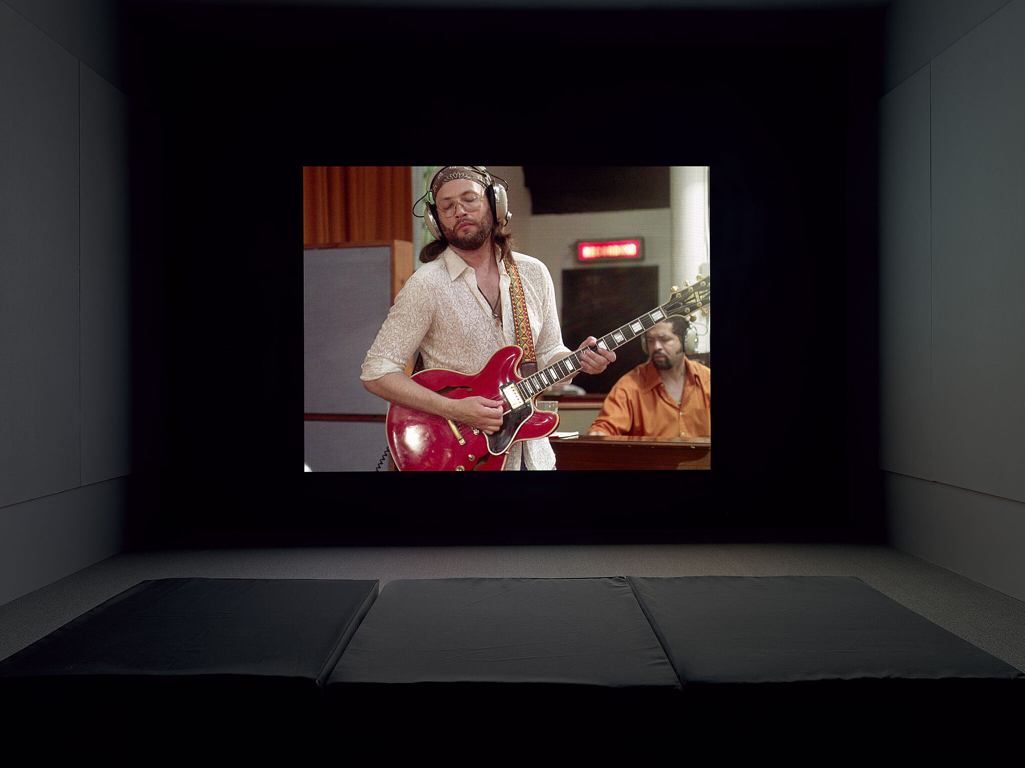 A video projection of a person playing guitar