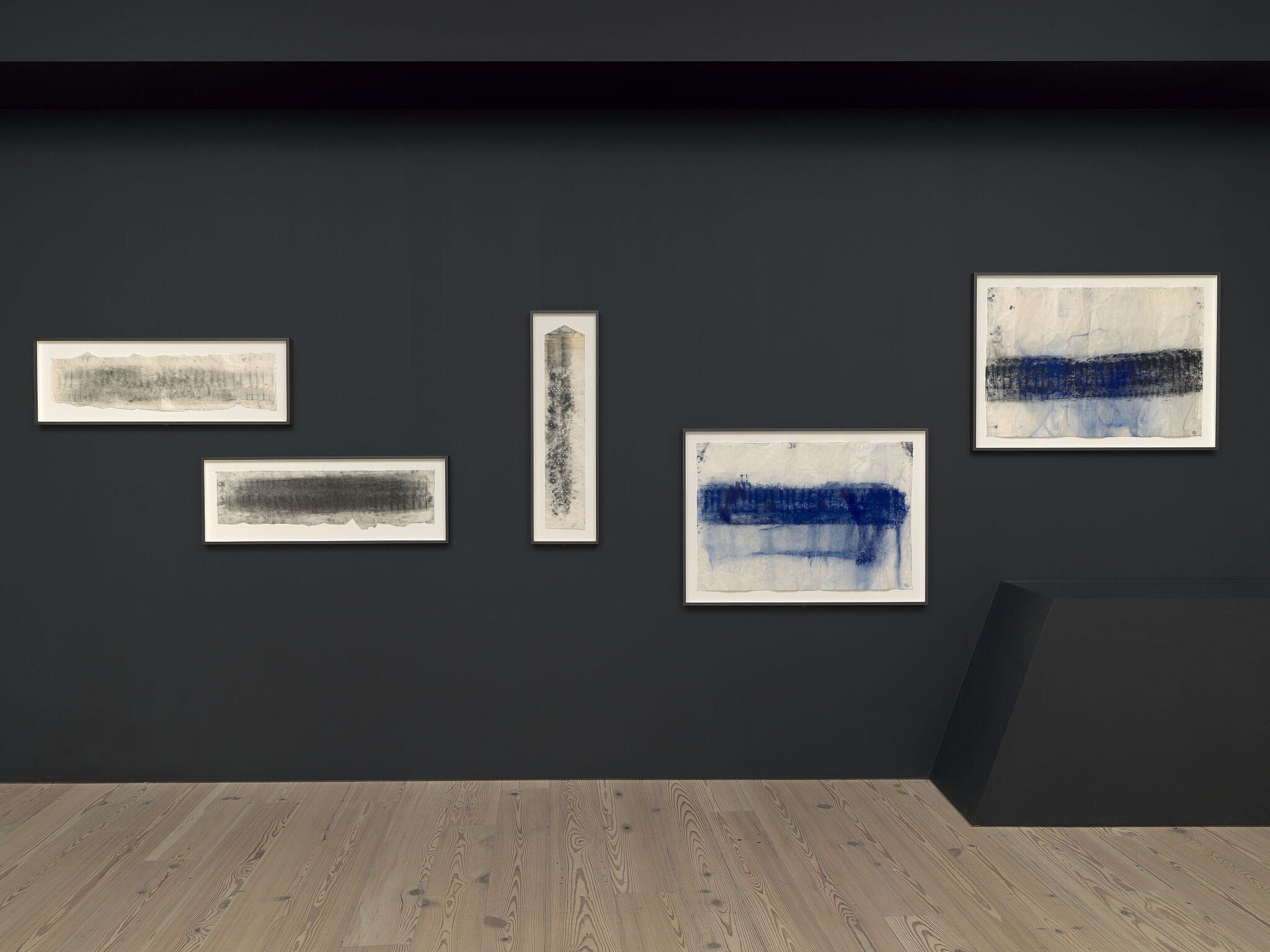 A wall of various charcoal drawings