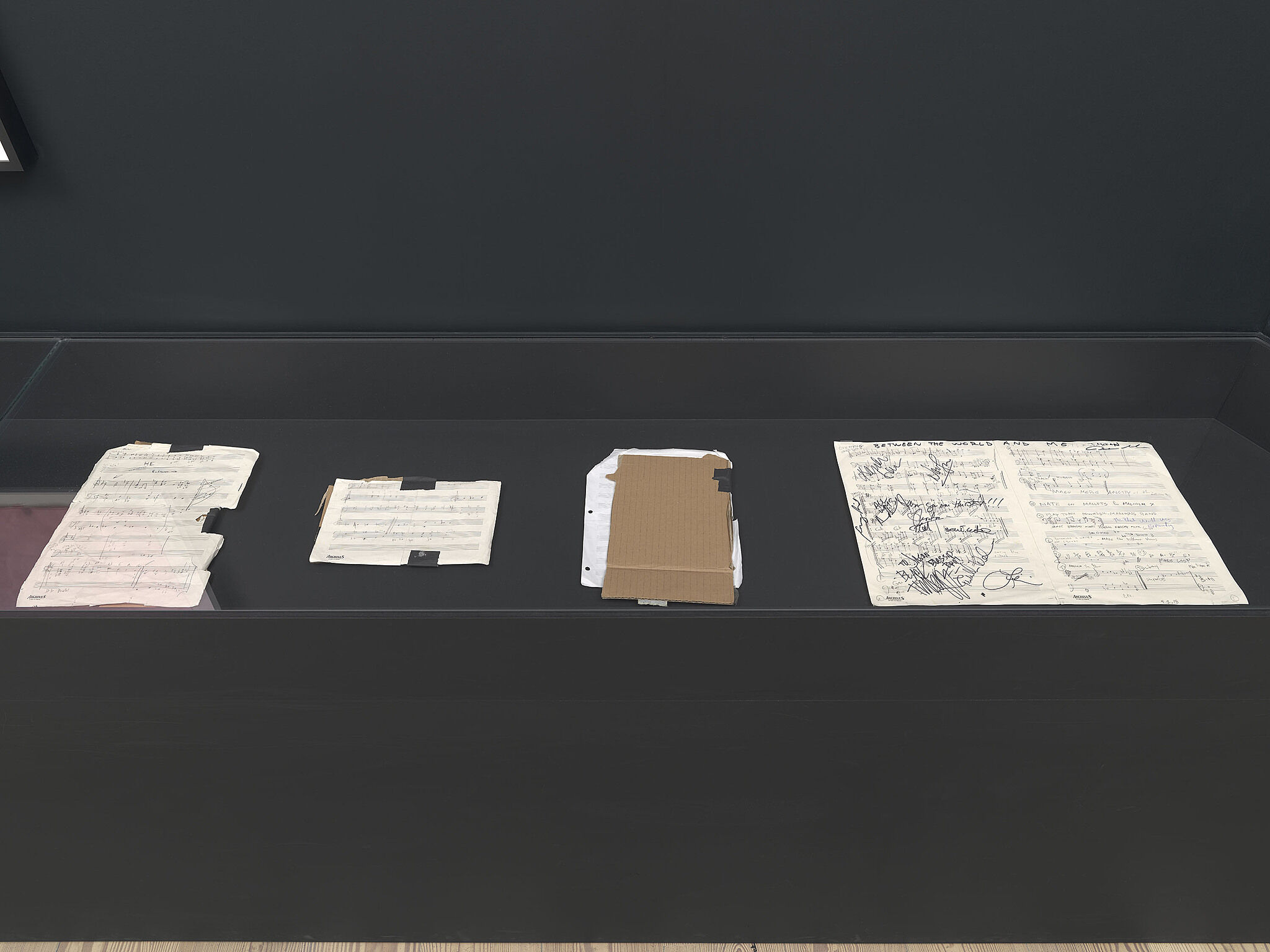 A glass case with various paper compositions