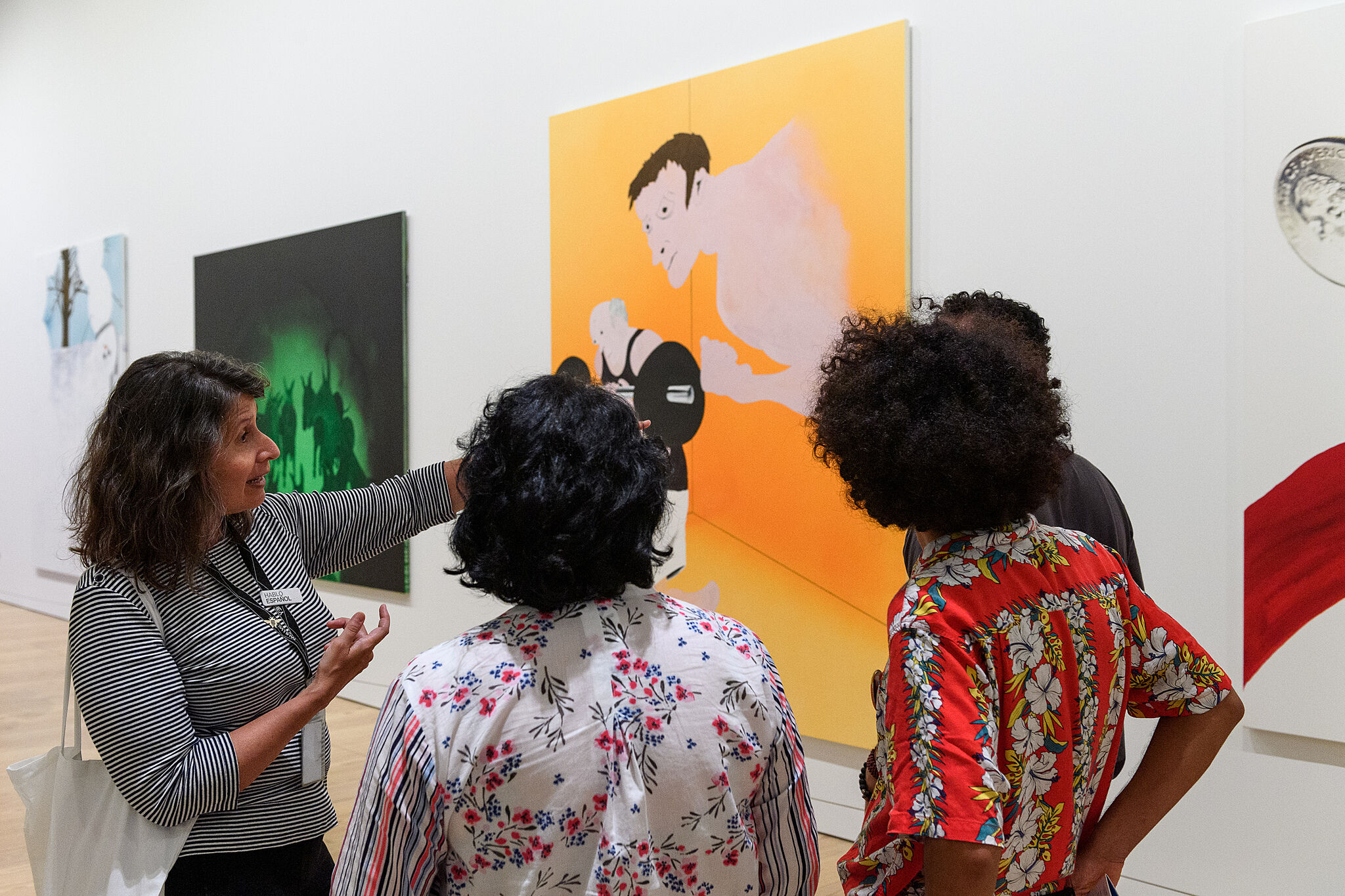 Four individuals stand around a painting speaking and pointing.