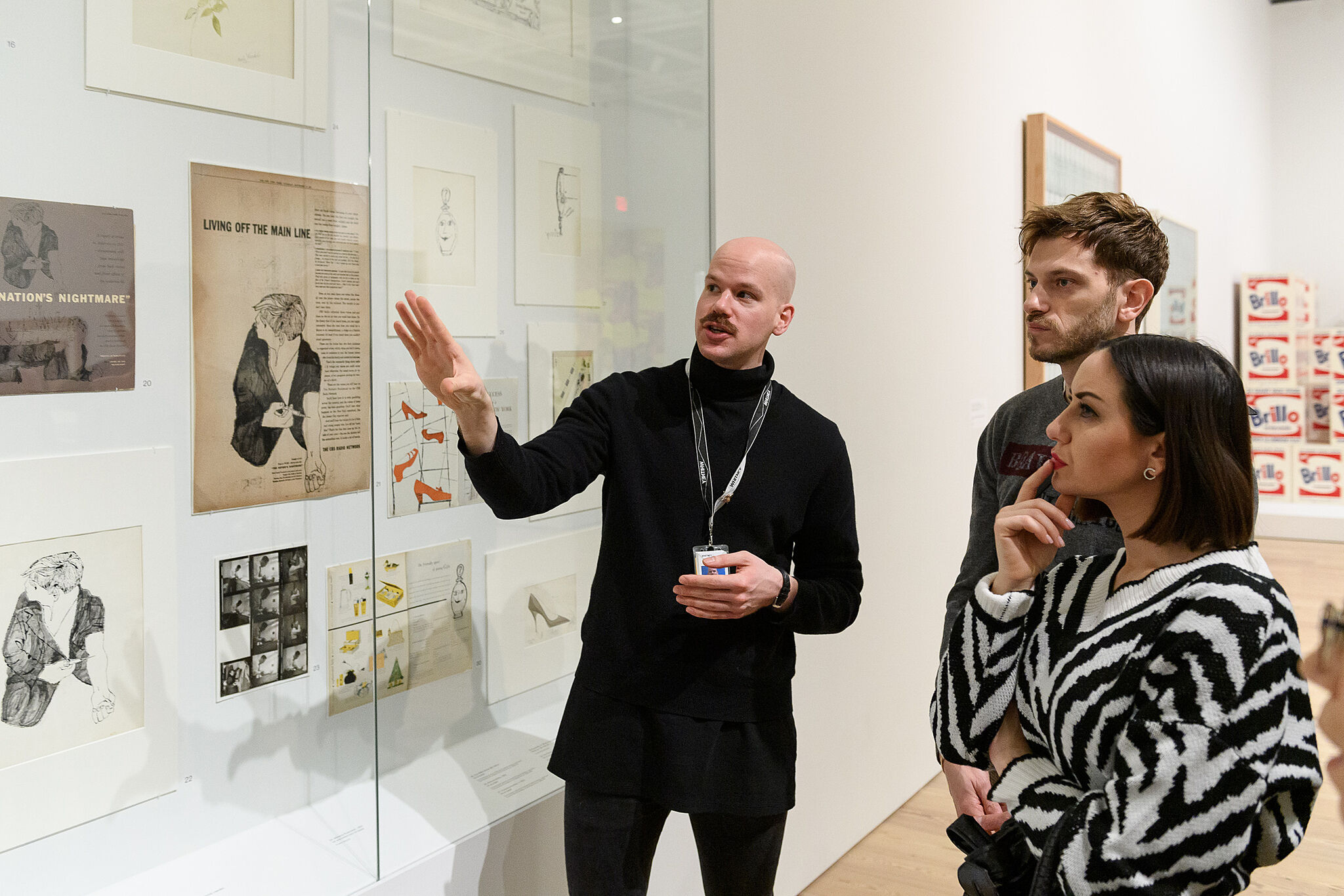 A person gestures towards a glass case of paper artworks while two other people look at the work.