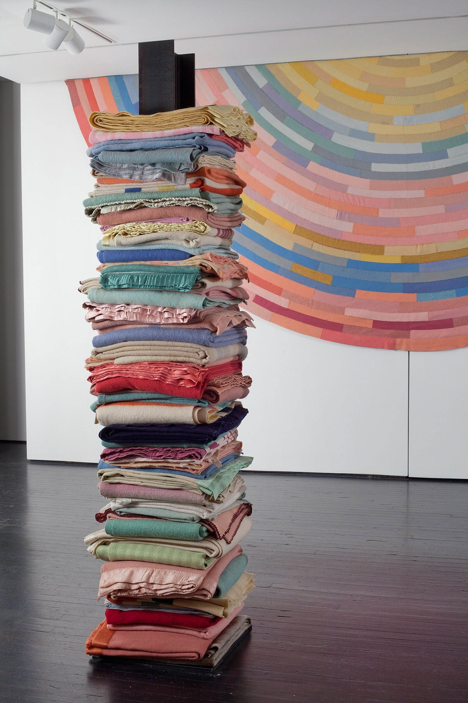A large stack of multi-colored blankets.