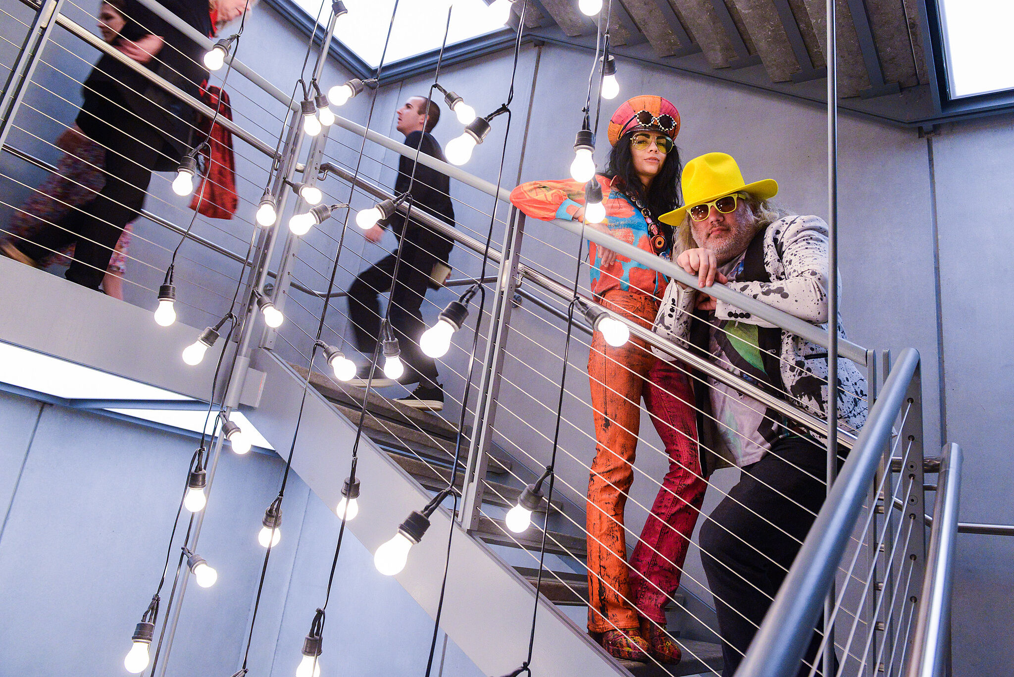 A photo of people standing on the Whitney's staircase dressed in costumes.