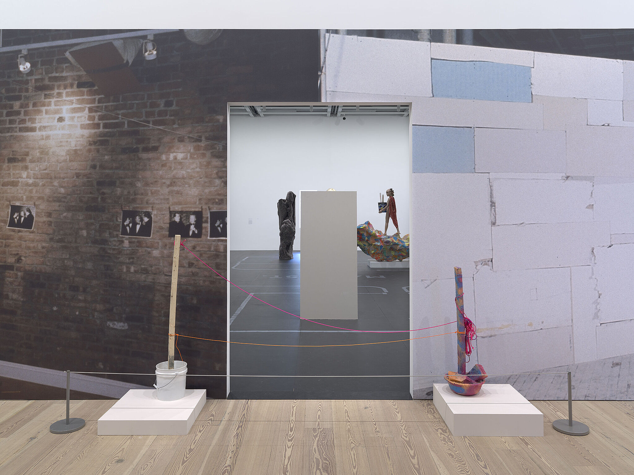 Installation view of the Whitney galleries with various sculptures and a doorway blocked by a stanchion.