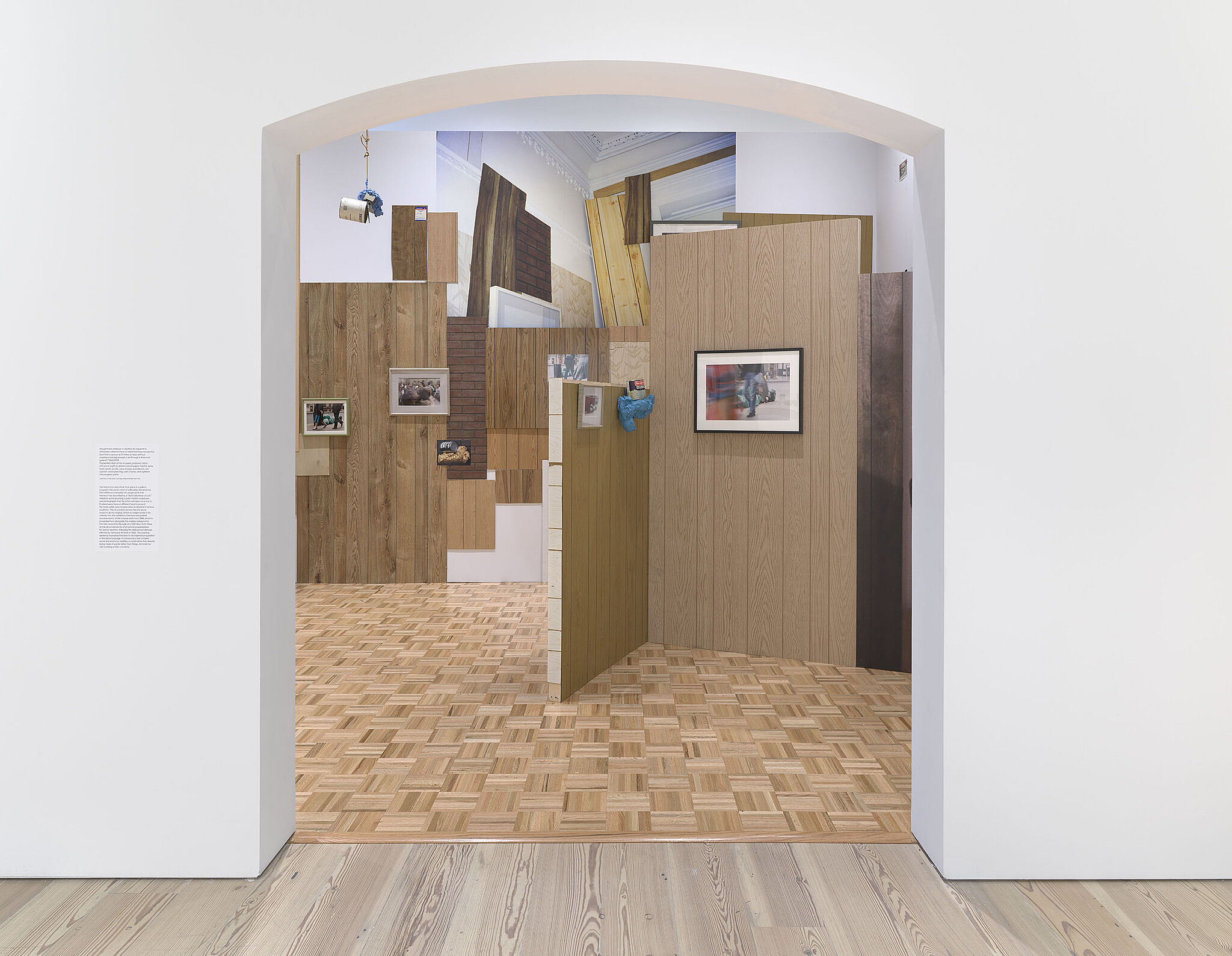 A gallery with fake wood walls, large photographs, and cans of peas.