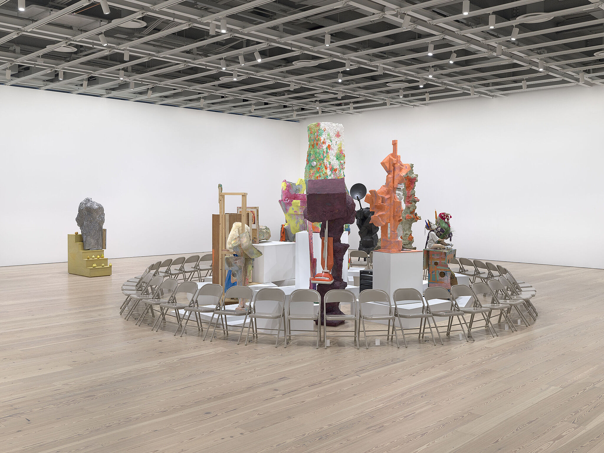 A ring of chairs surround various sculptures in a gallery.