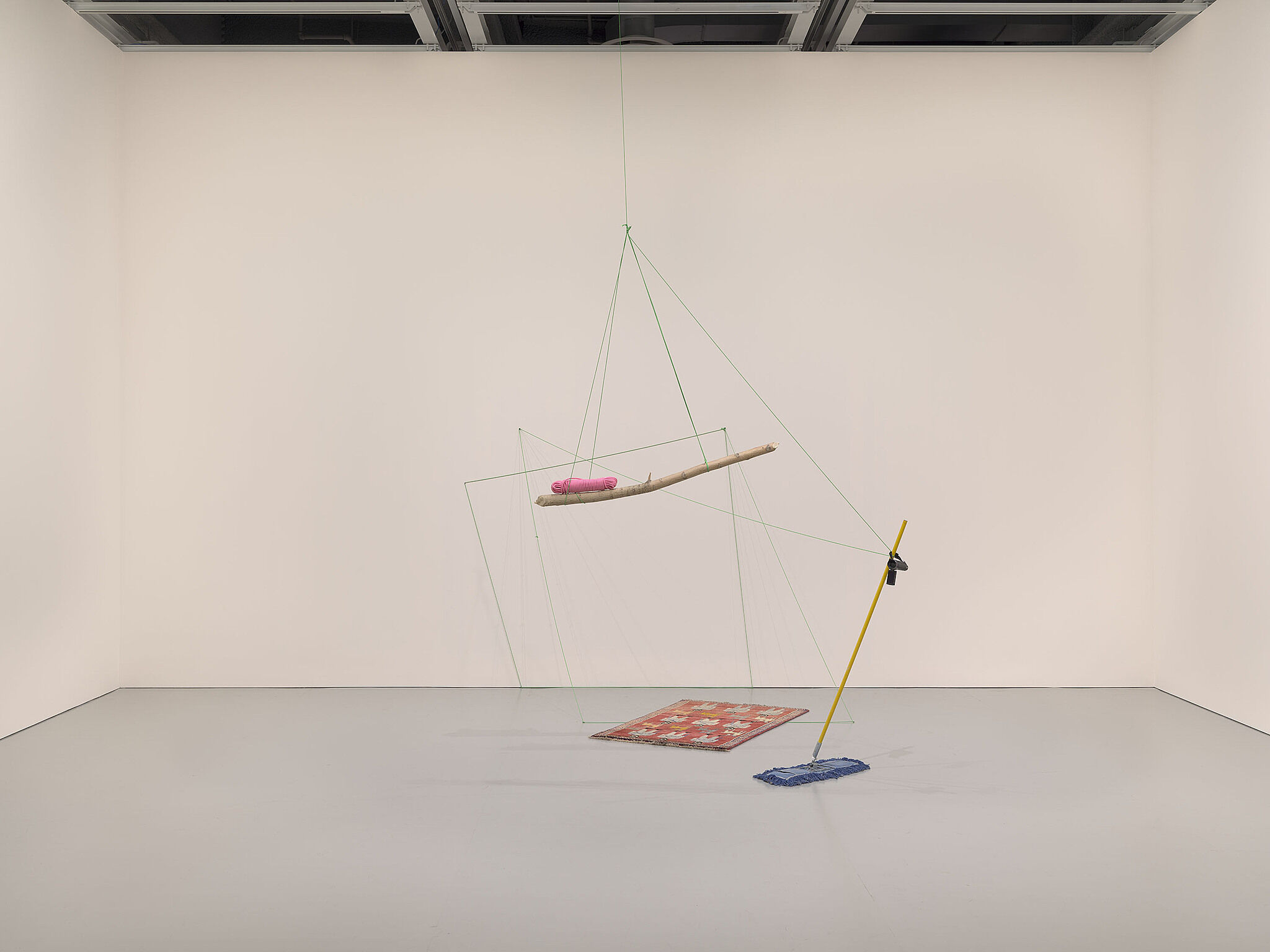 A gallery with a single sculpture made of a rug, a mop, and a stick tied to the ceiling with string.