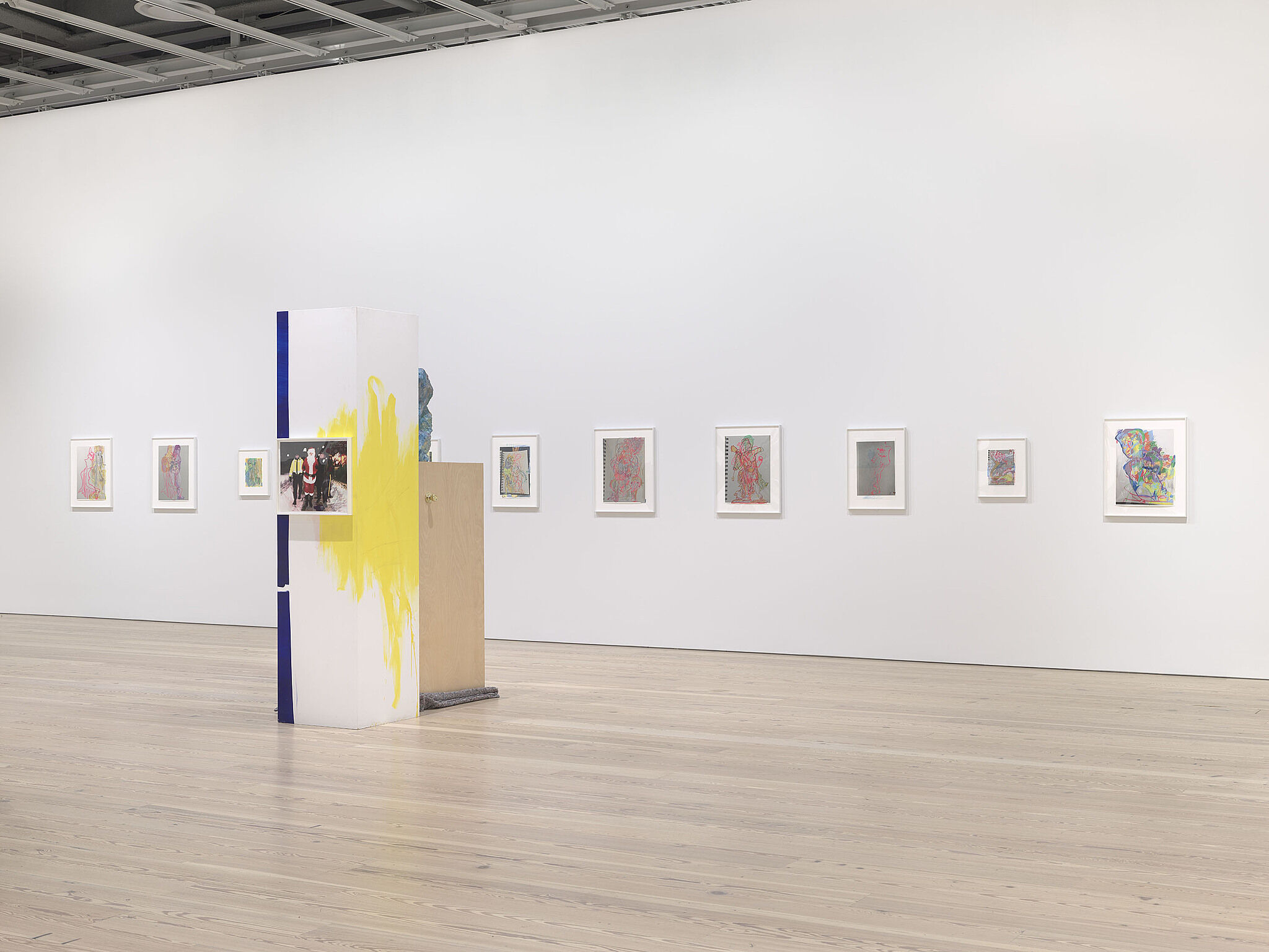 An image of the Whitney galleries with various artworks on the wall and a single sculpture.