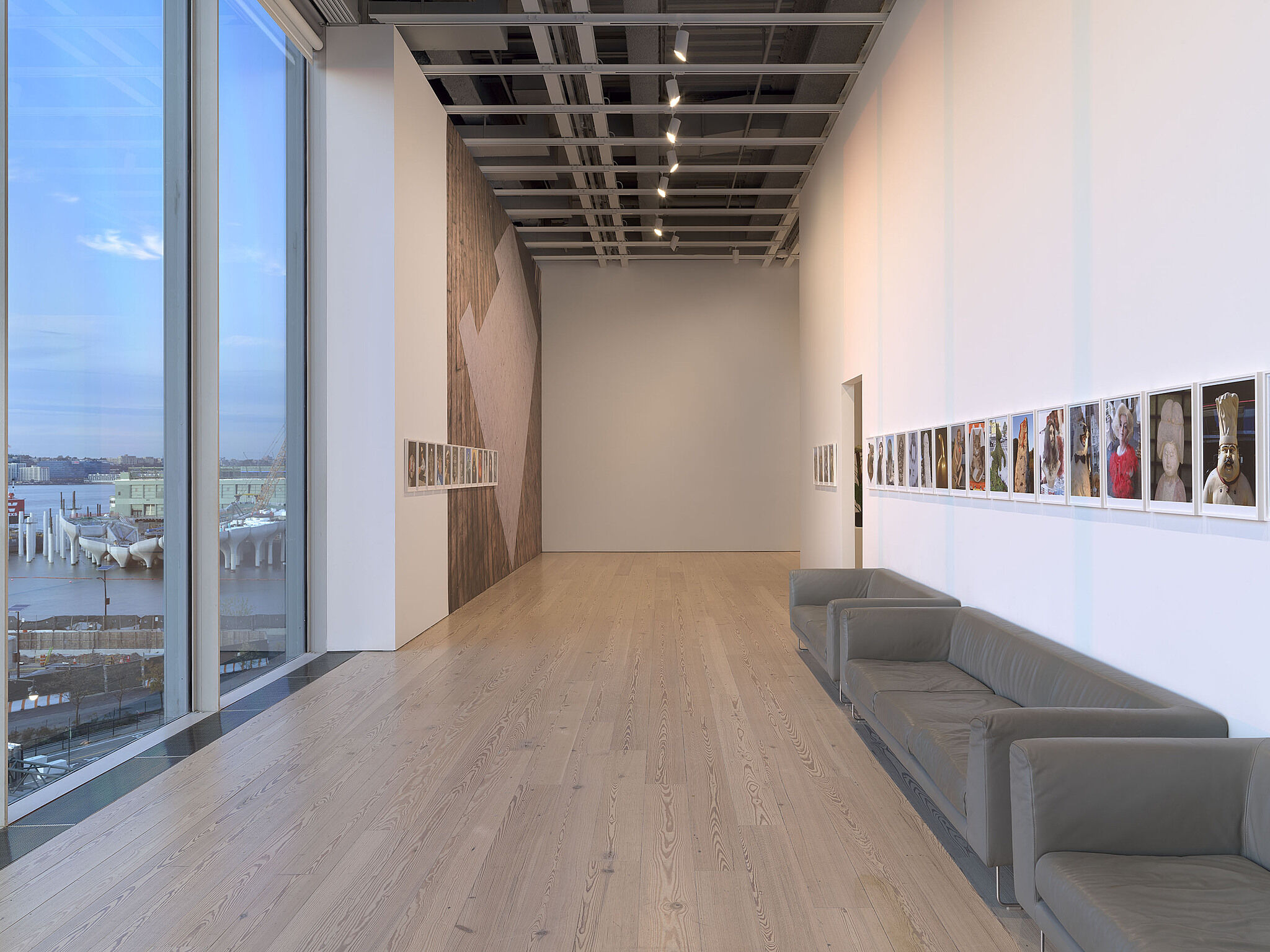 The Whitney gallery facing the river with a line of artworks on the wall.