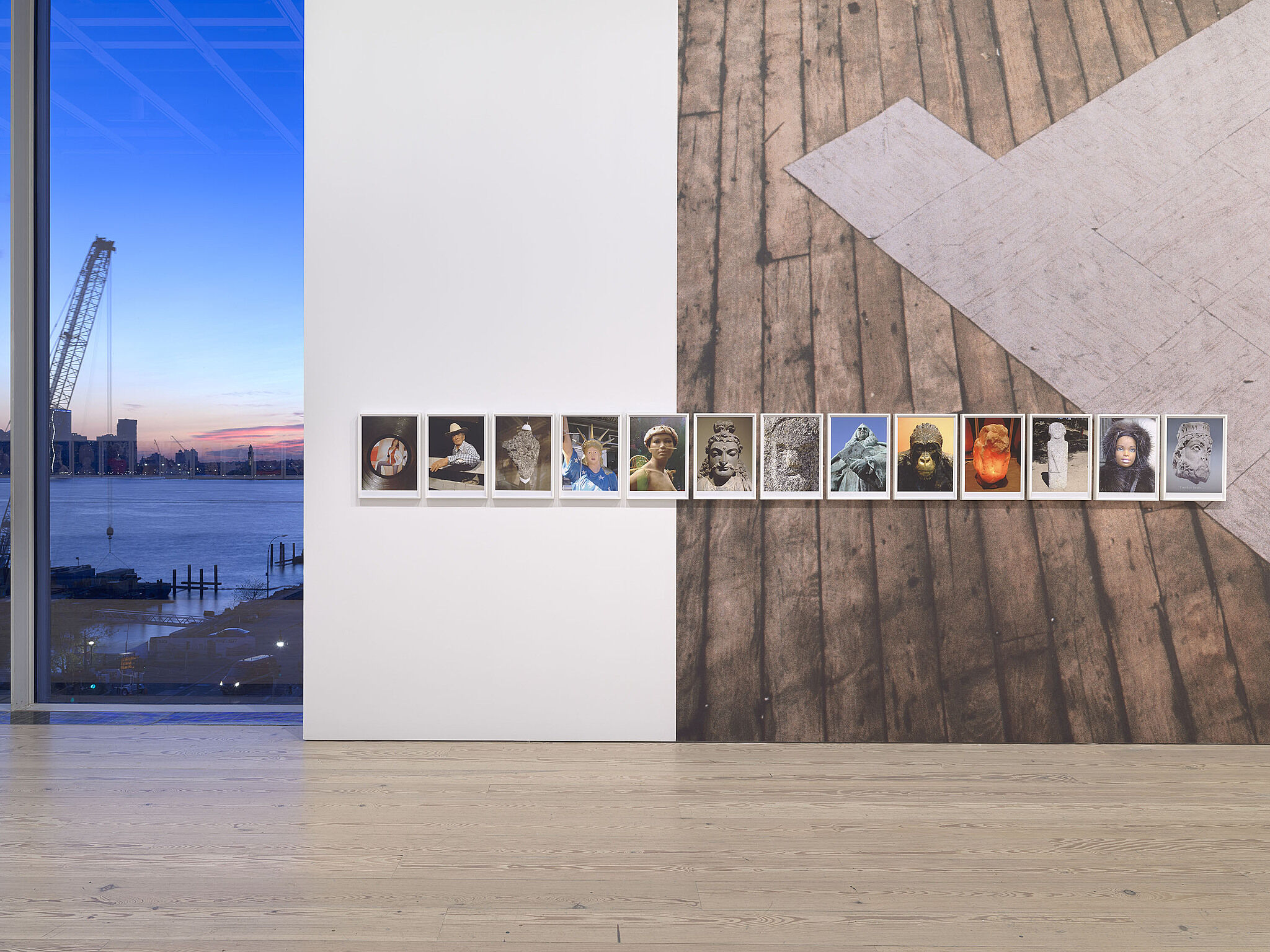 A large photo of wood flooring on a gallery wall and a line of smaller photographs.