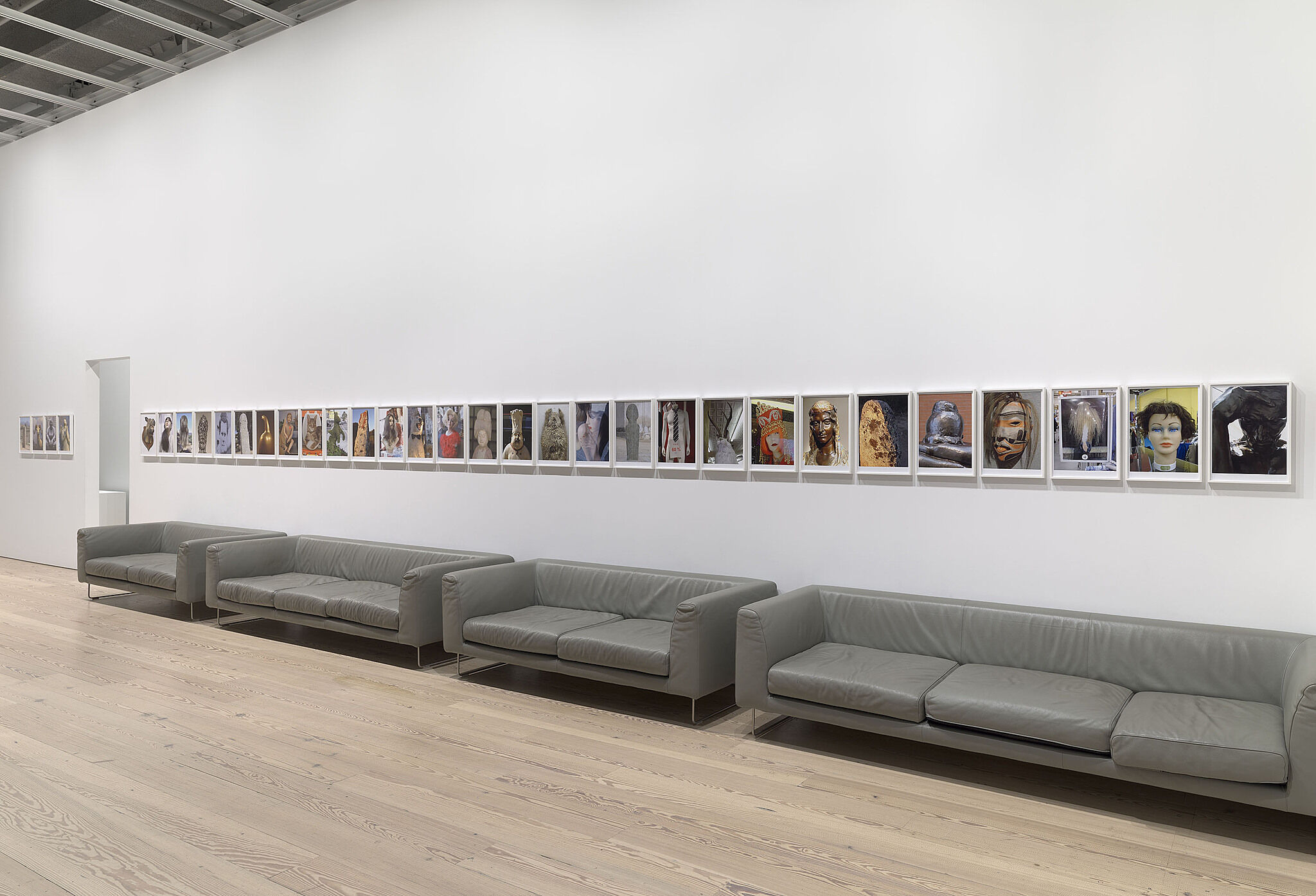Multiple couches in a gallery with a line of small photographs on the wall.