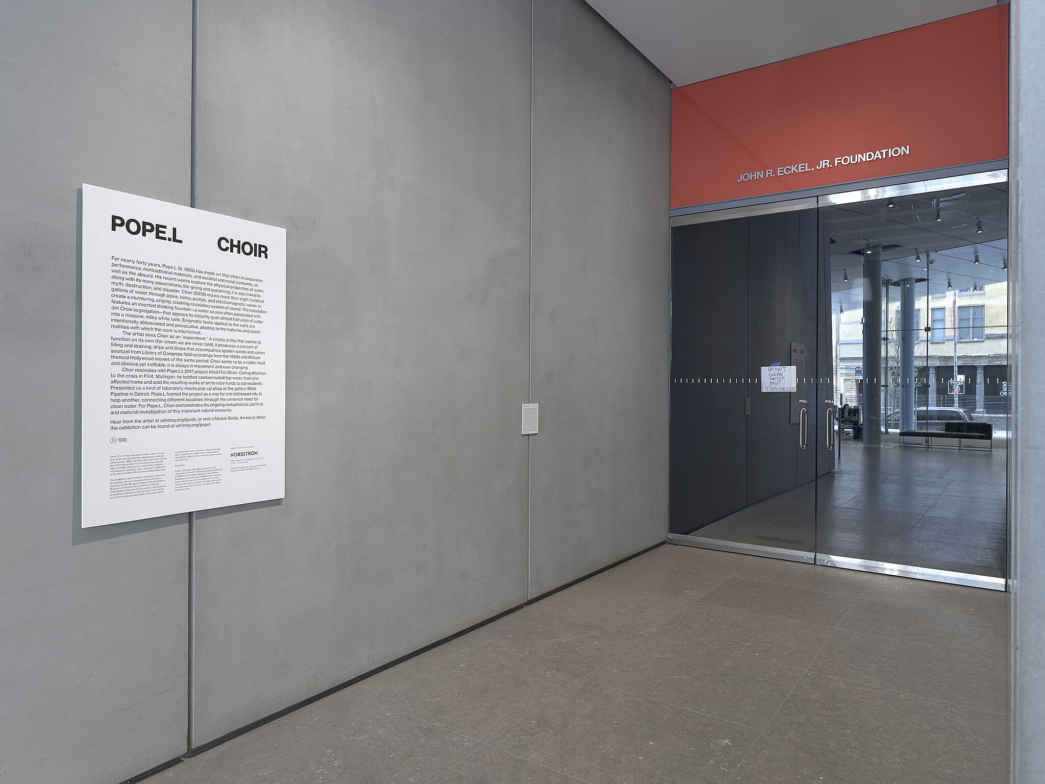 The entryway to a gallery exhibition with signage.