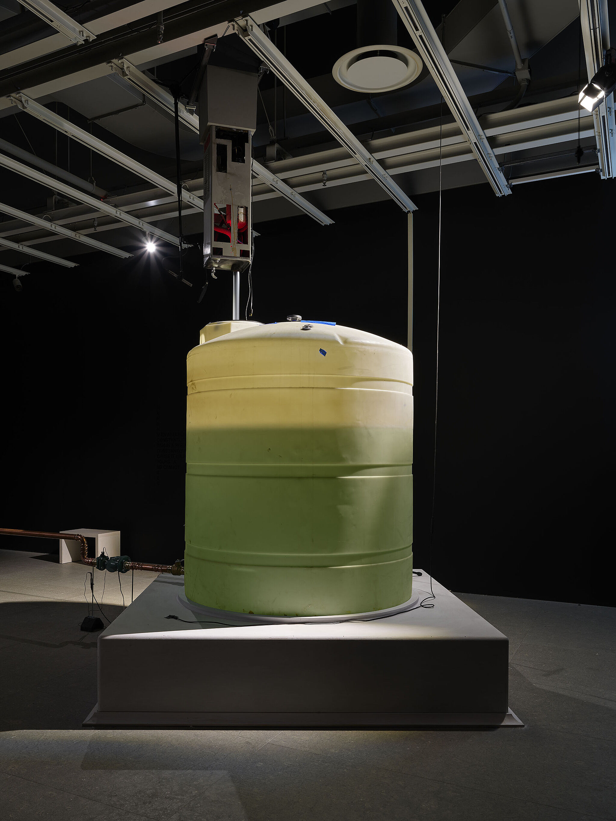 A large water tank in a dark room with pipes.