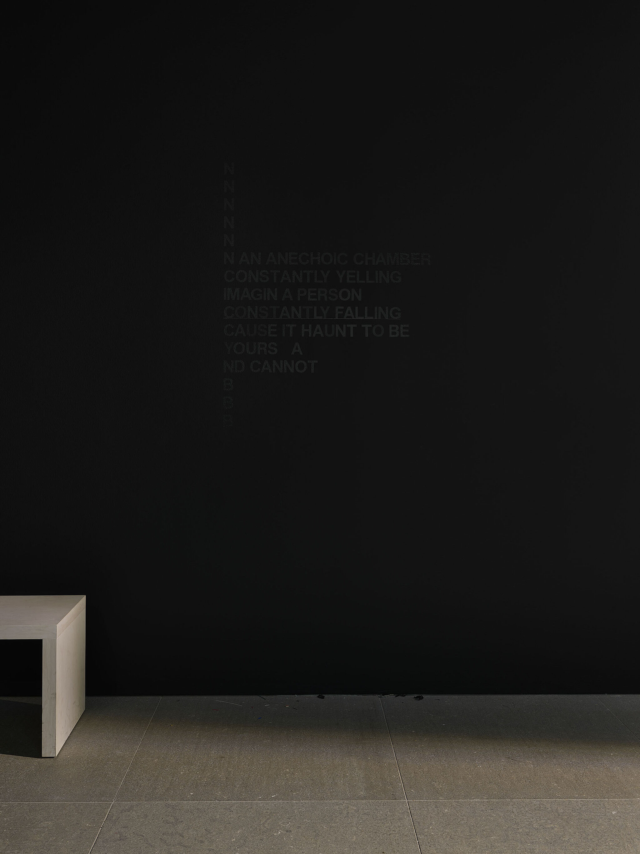 A black wall with black vinyl words.