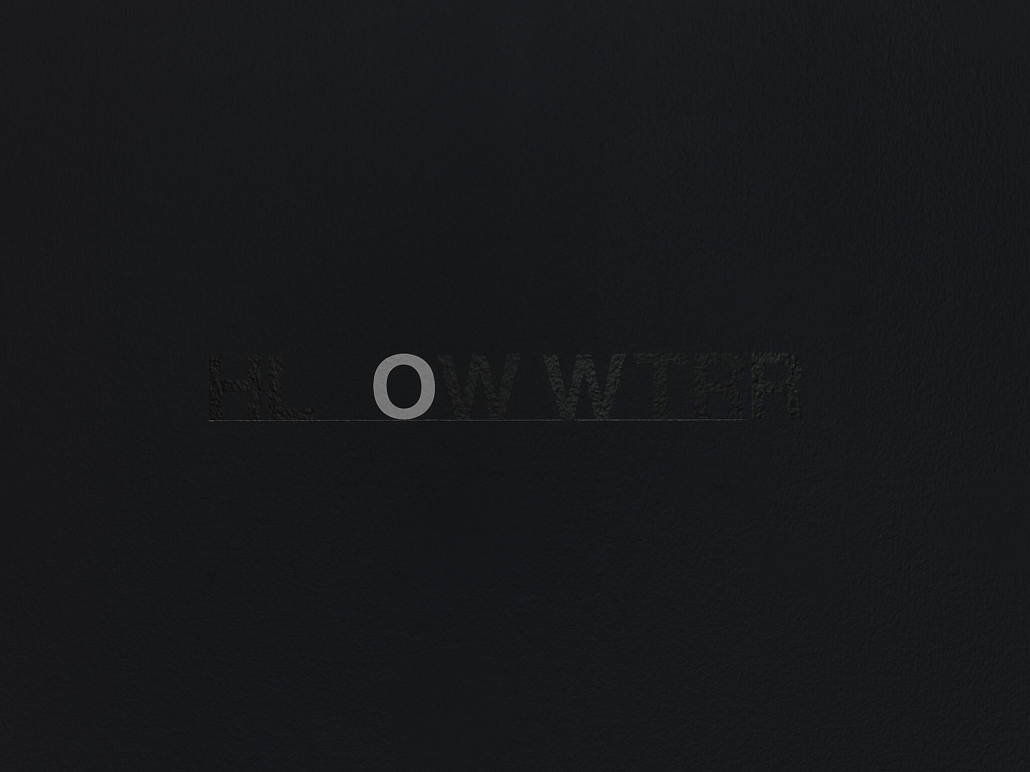 """A black wall with black vinyl letters and a single white vinyl """"O."""""""