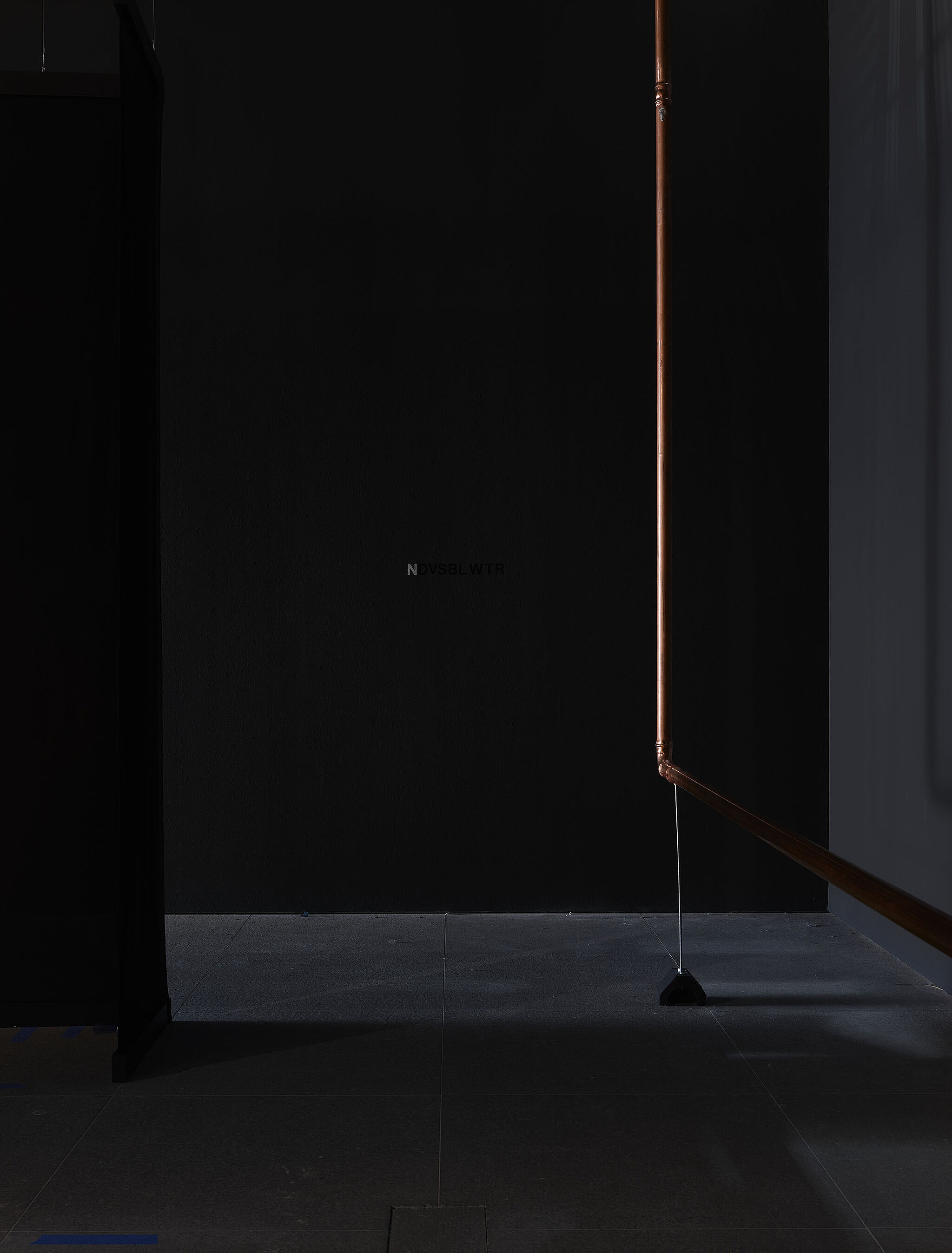 A copper pipe in a dark room.