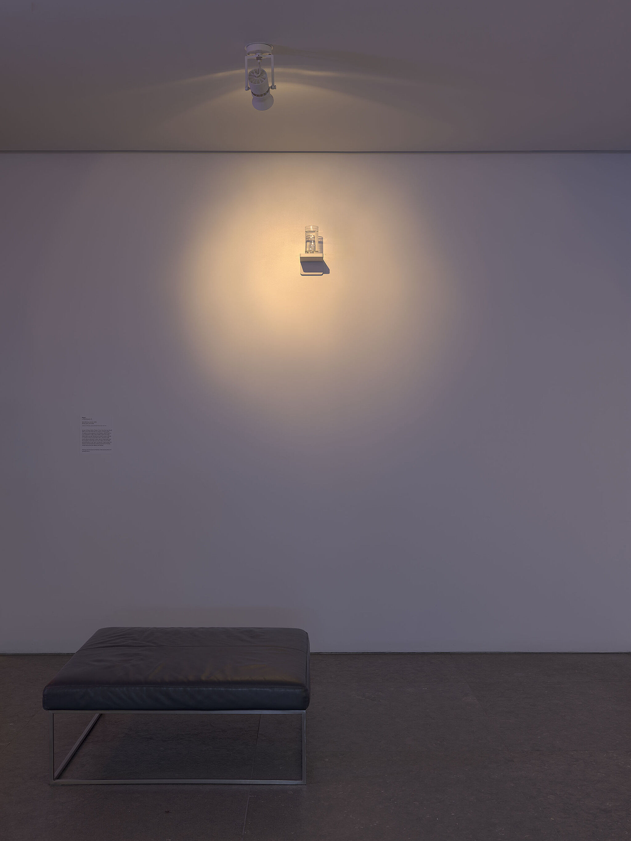 A glass of water sitting on a high shelf in a gallery.