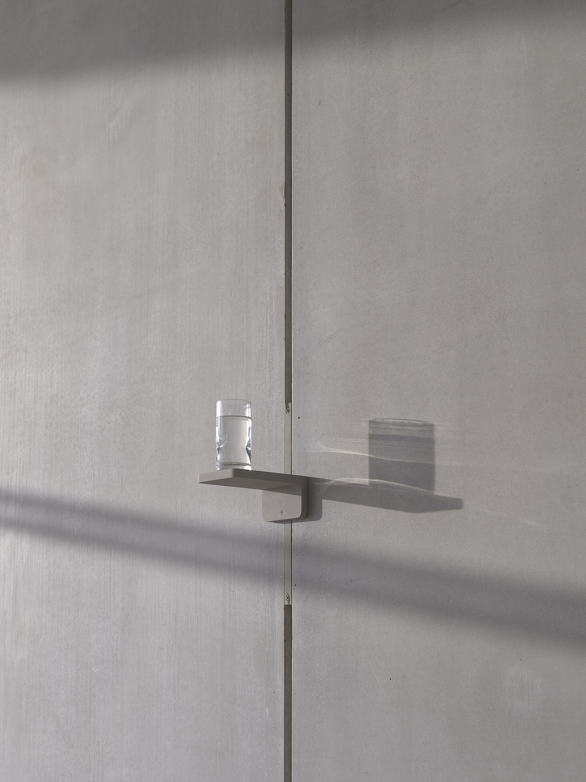A glass of water sitting on a high shelf in the Whitney lobby.