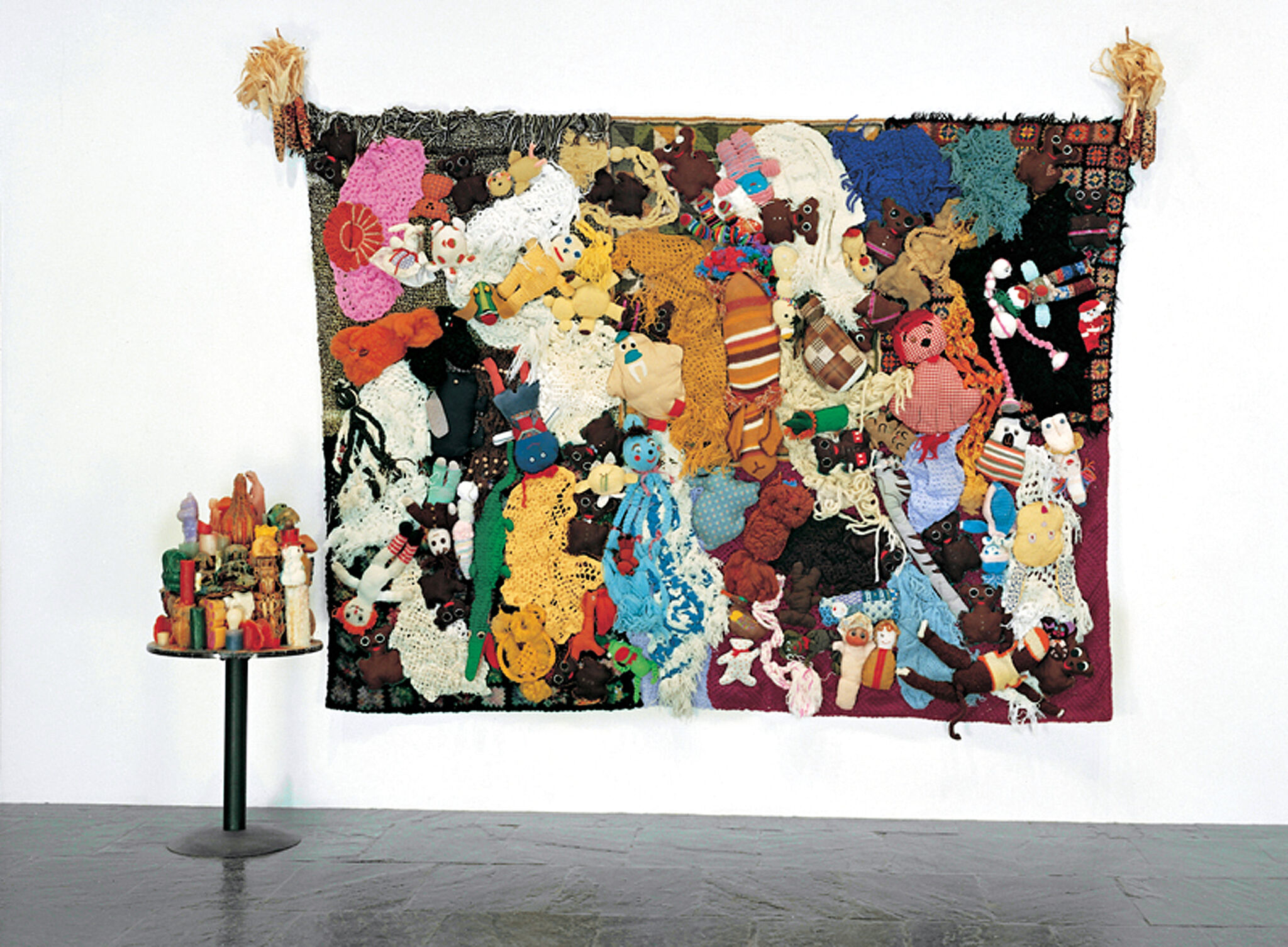 A wall with a sculpture made of stuffed animals and a table with a sculpture made of wax candles.
