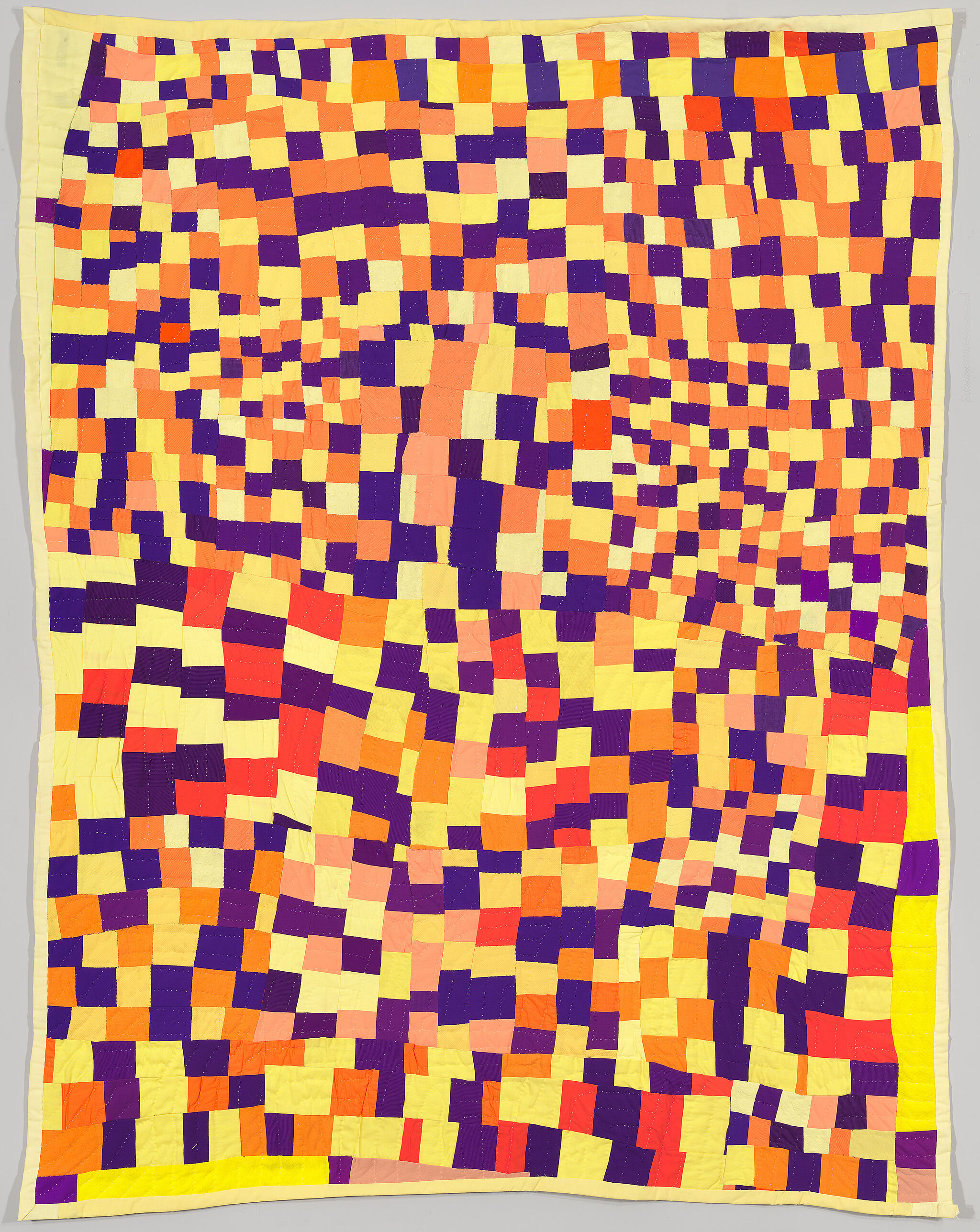 A photo of a yellow and orange patterned quilt.