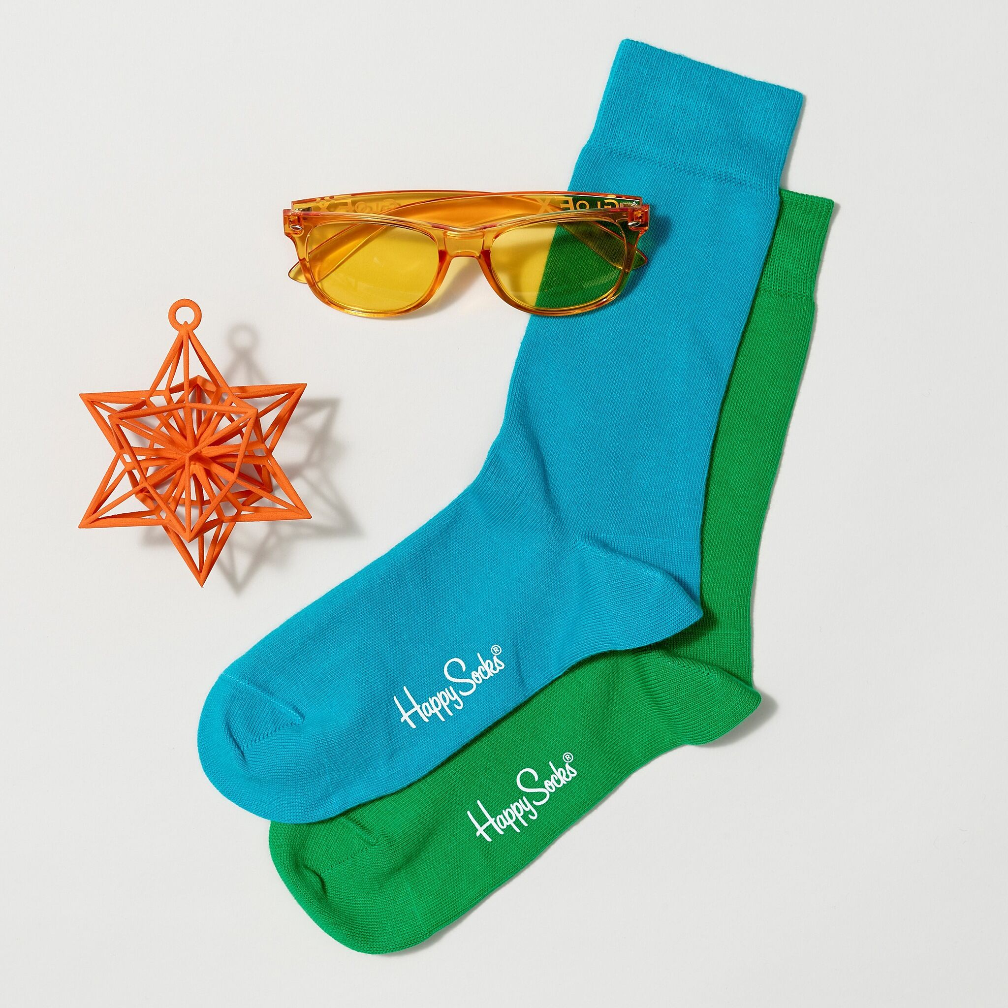 A photo of colorful socks, colored sunglasses, and a Christmas ornament.