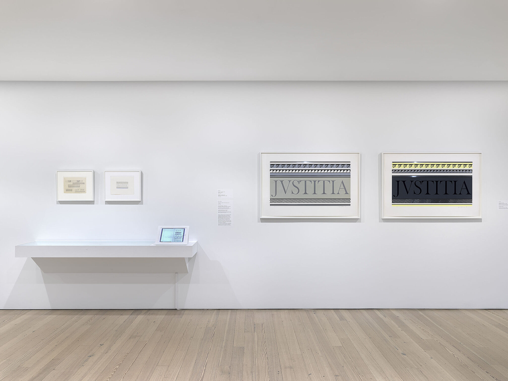 A photo of the Whitney gallery with various artworks on the wall.