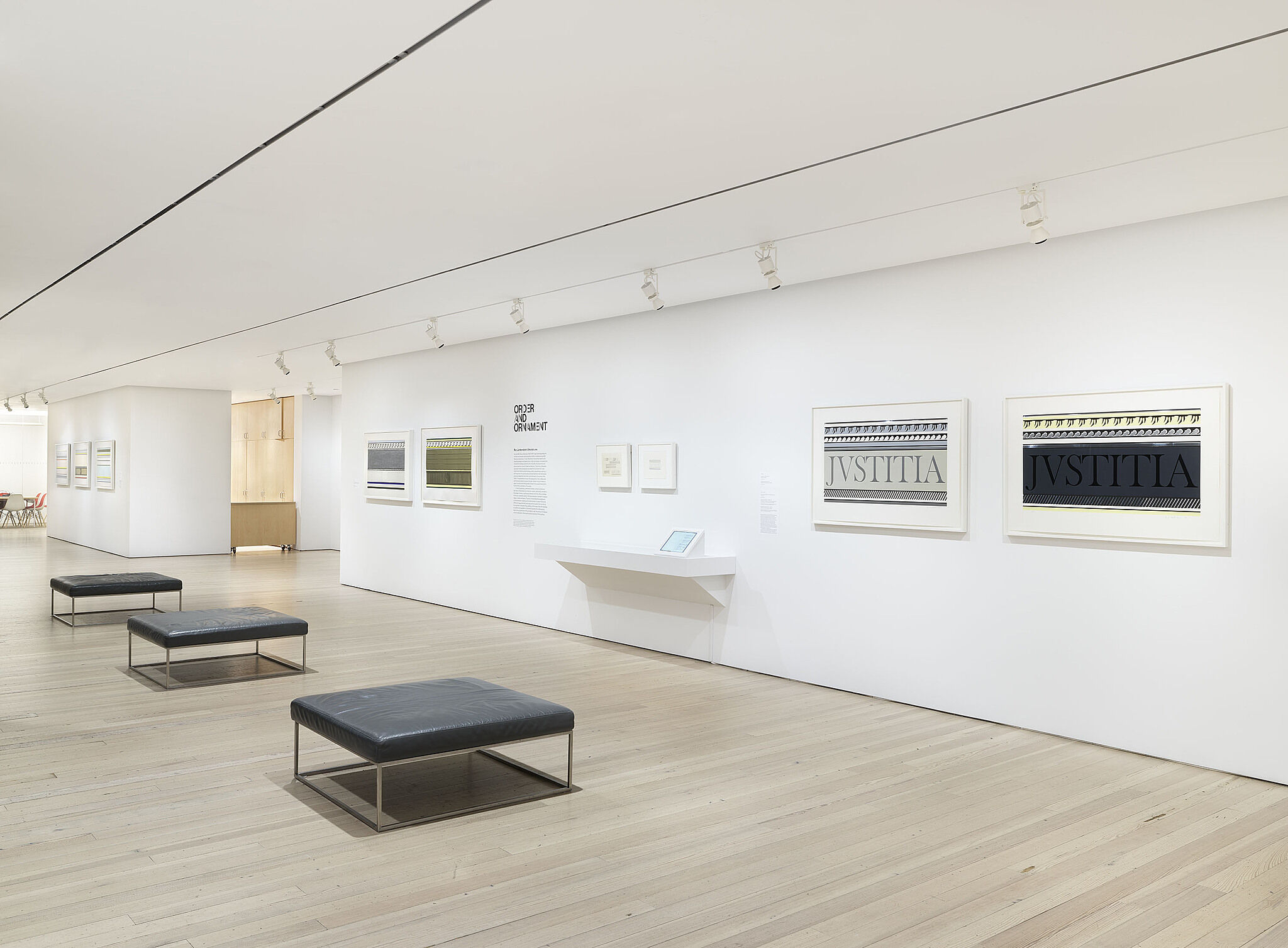 A photo of a Whitney gallery with various artworks on the wall.