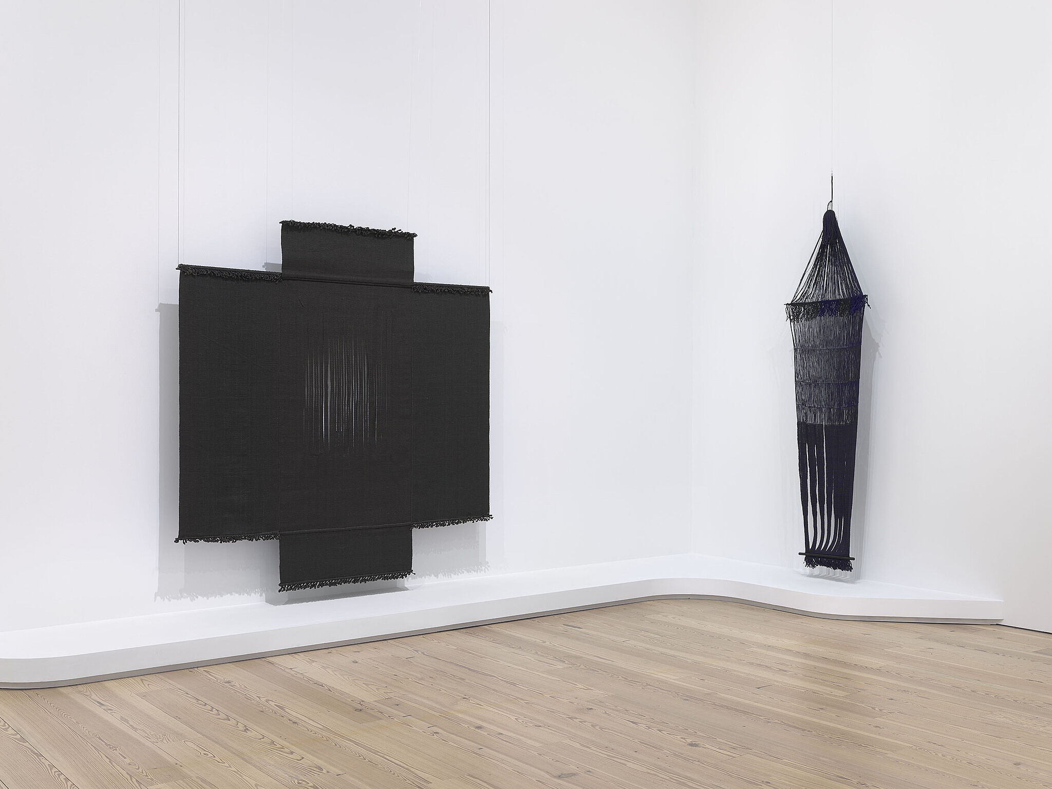 A photo of a Whitney gallery with two tapestry-like sculptures hanging on the wall.
