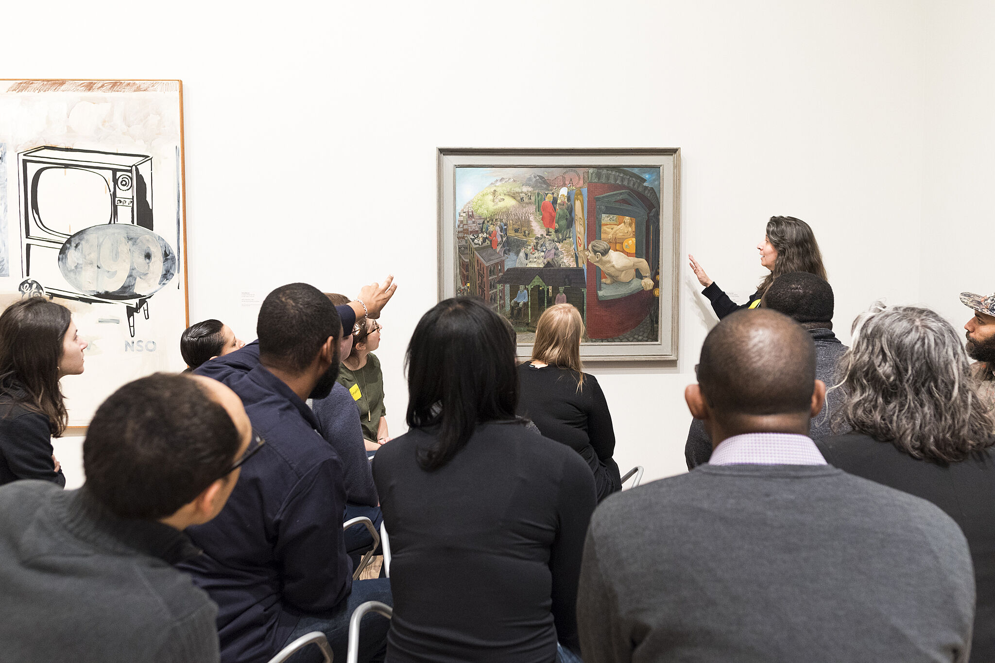 A photo of a woman pointing at a painting while a small group looks at the piece.