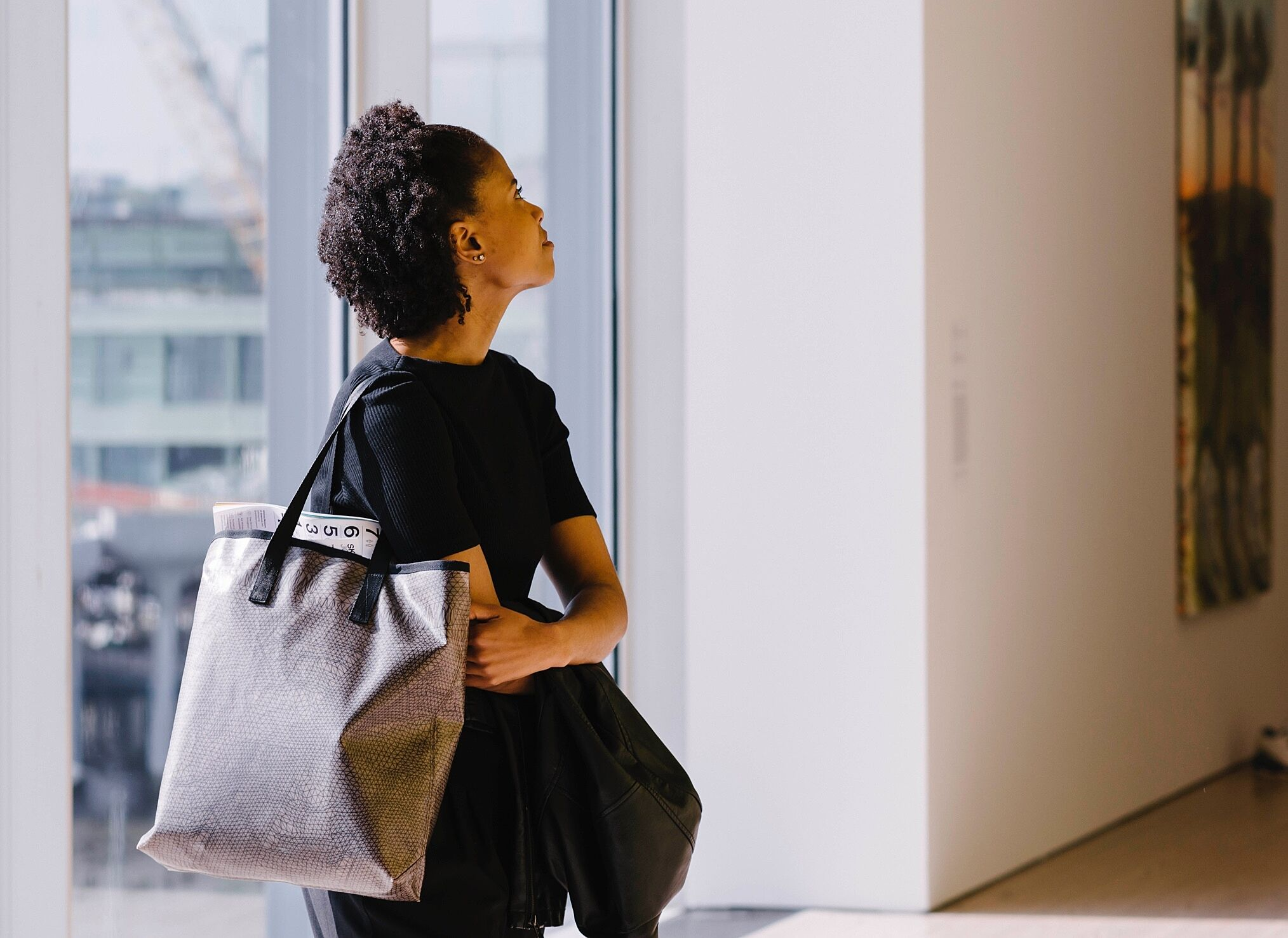 A woman carrying a tote bag looking around at art in the galleries.