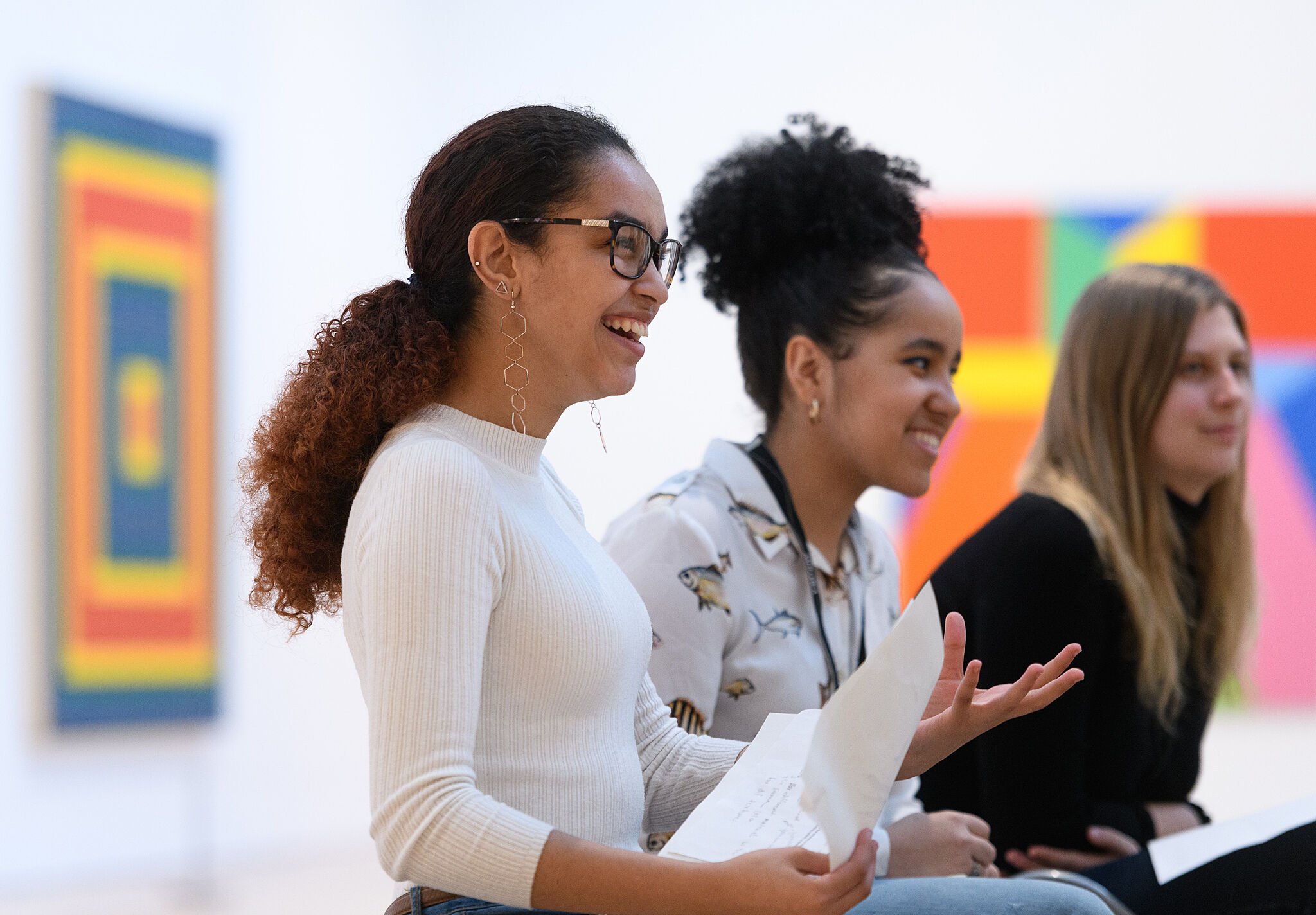A photo of three teenagers in the Whitney galleries smiling and laughing.