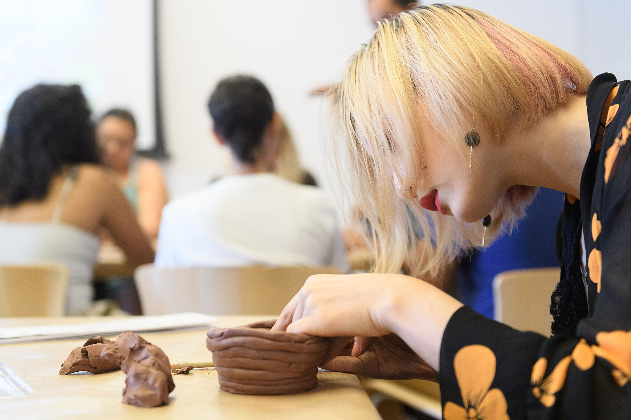 A photo of a teenager making a coil pot out of clay.