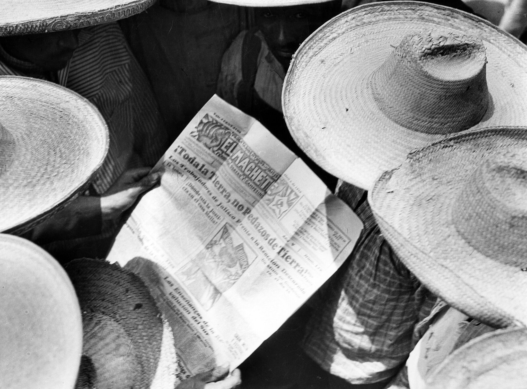 A black and white photo of people in hats reading a newspaper.