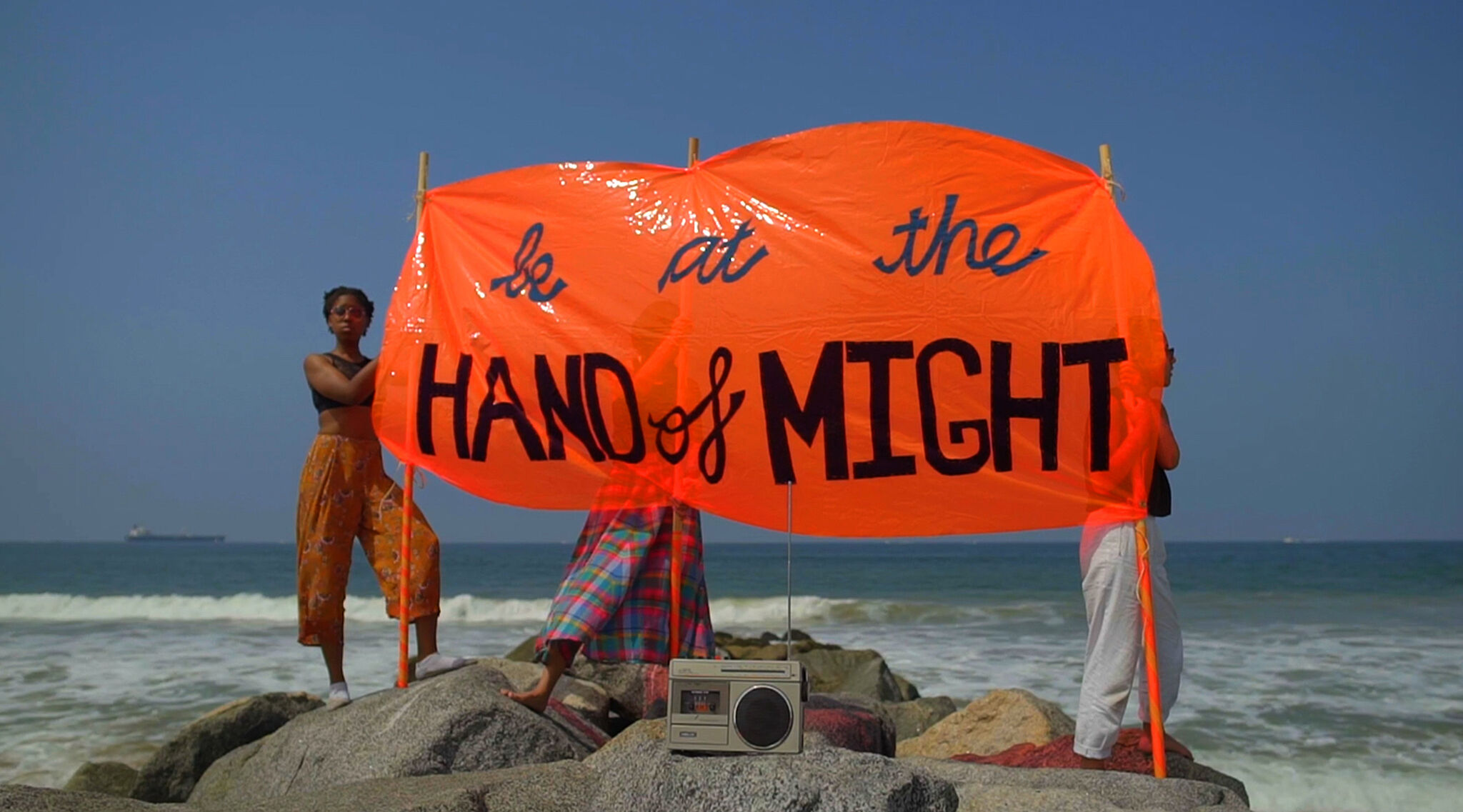 "A video still of three people holding a sign that reads ""be at the HAND of MIGHT."""