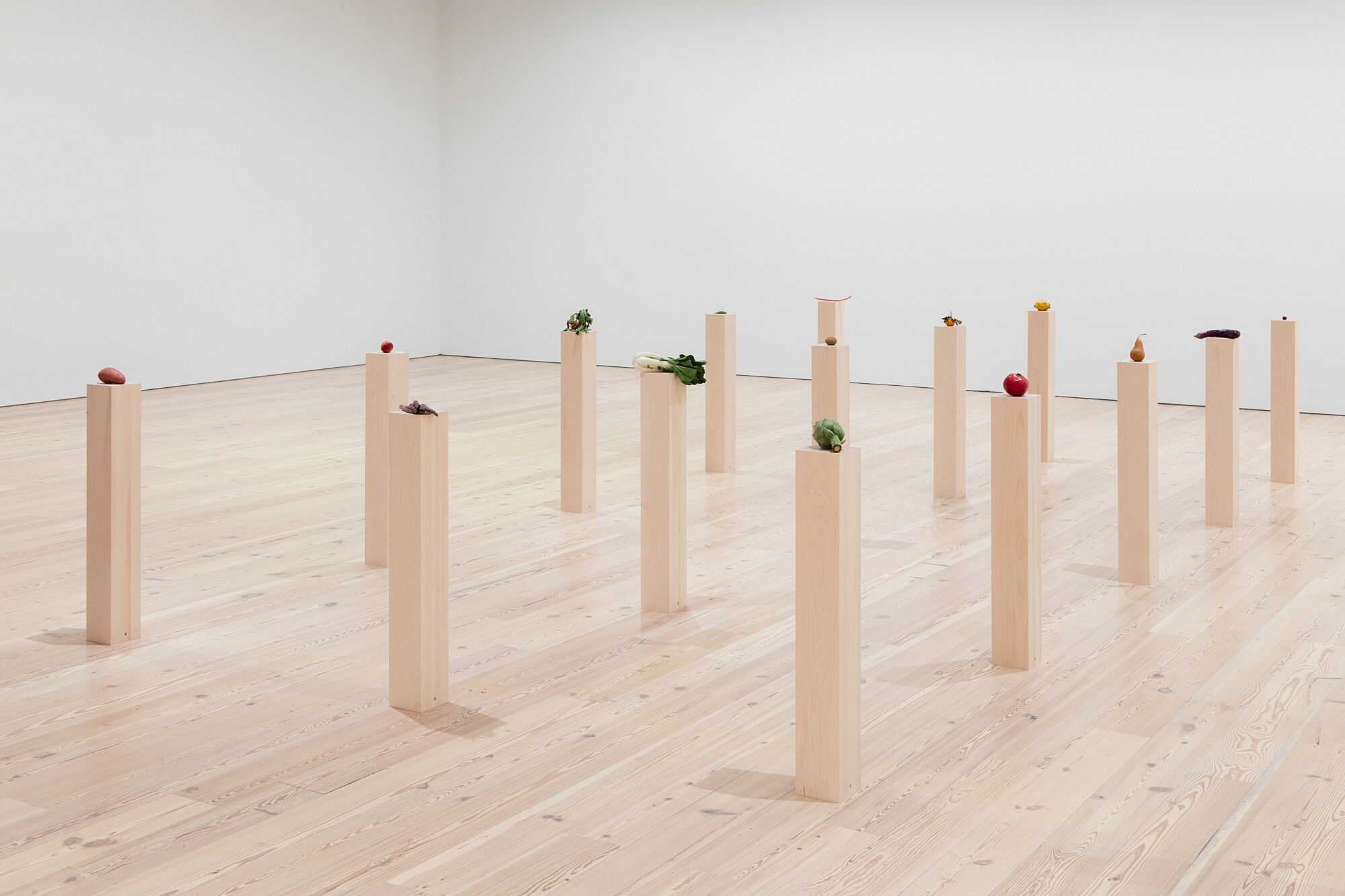 A photo of a gallery full of assorted vegetables and fruits on plinths.