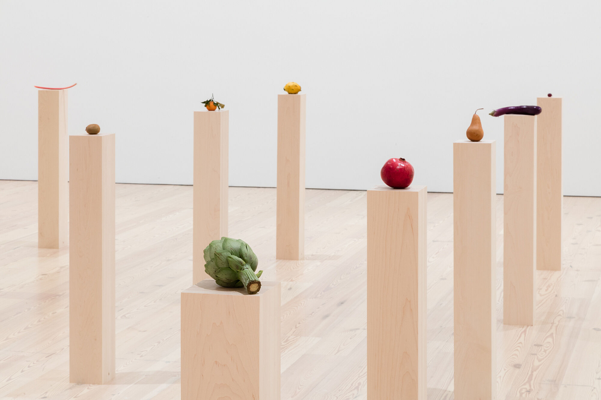 A photo of assorted vegetables and fruits on plinths.