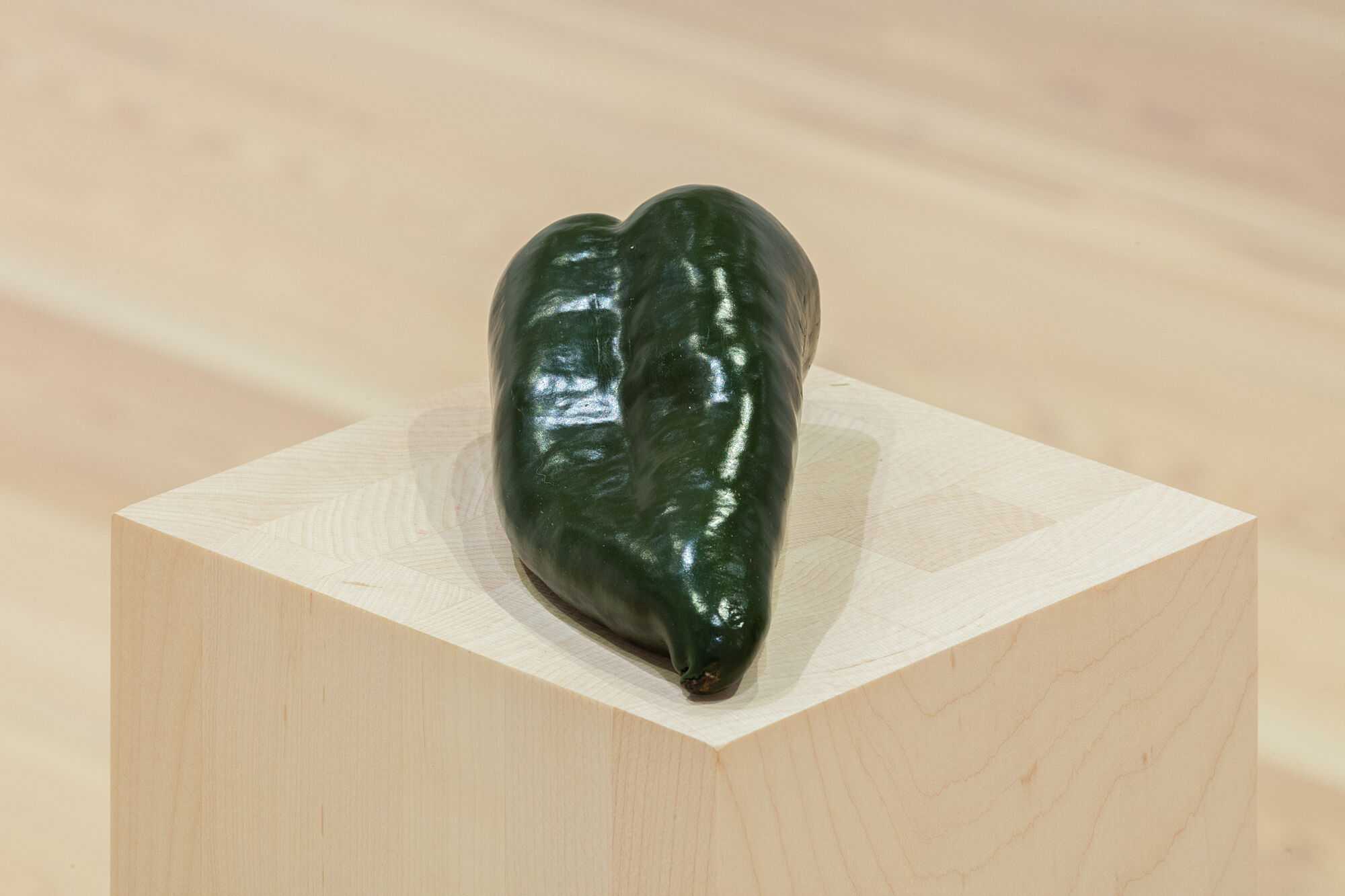 A photo of a poblano pepper on a plinth