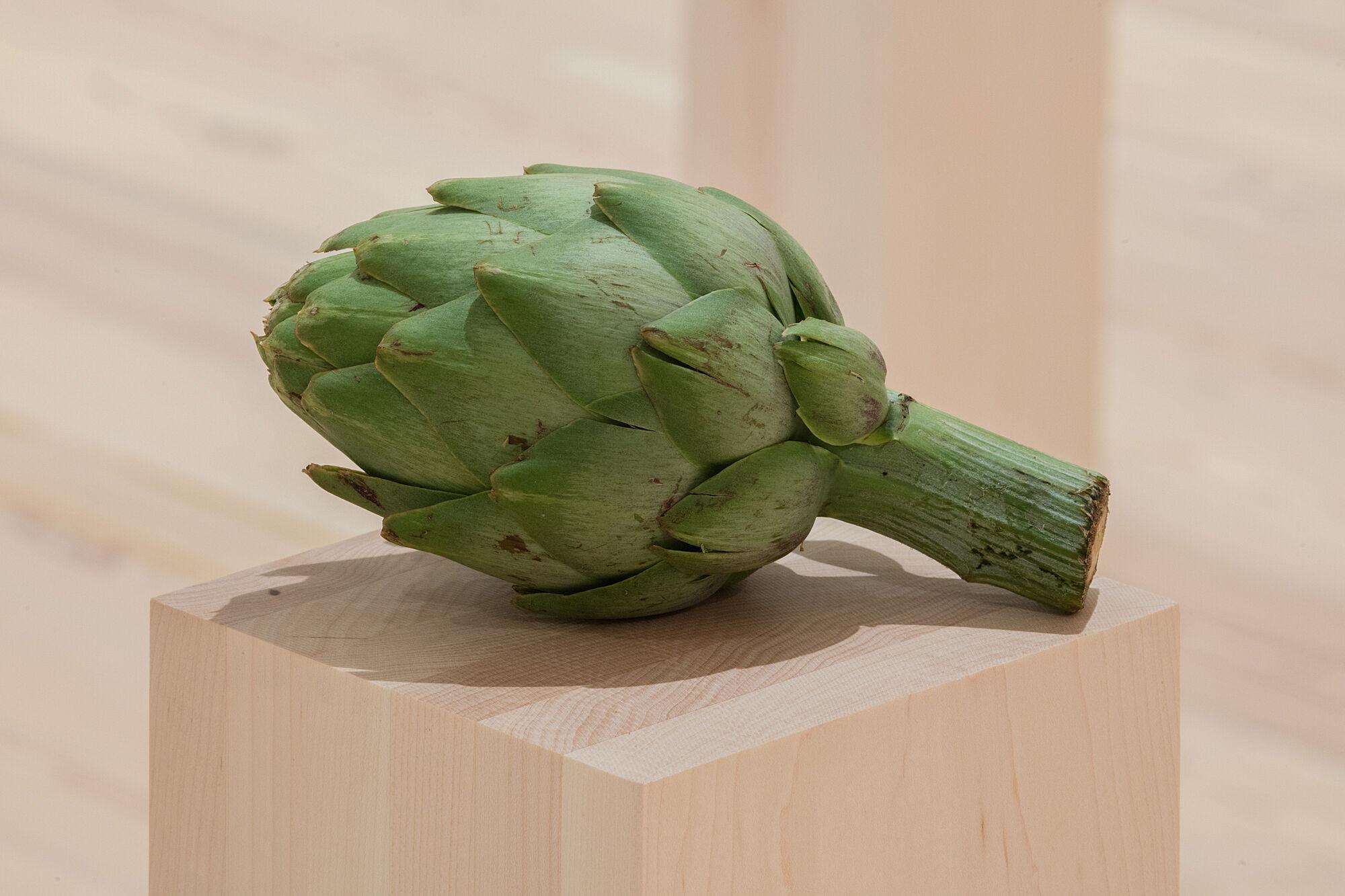 A photo of an artichoke on a plinth.
