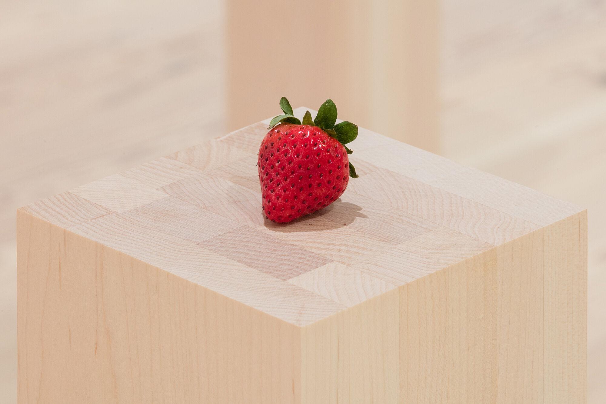 A photo of a strawberry on a plinth.