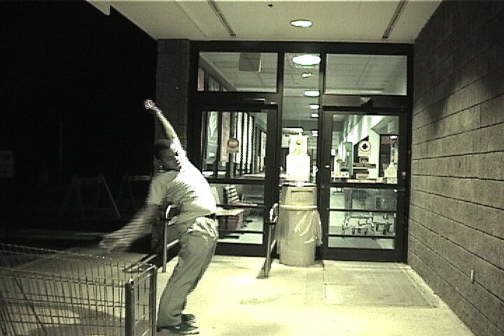 A grainy still of a man outside a supermarket with a shopping cart in view