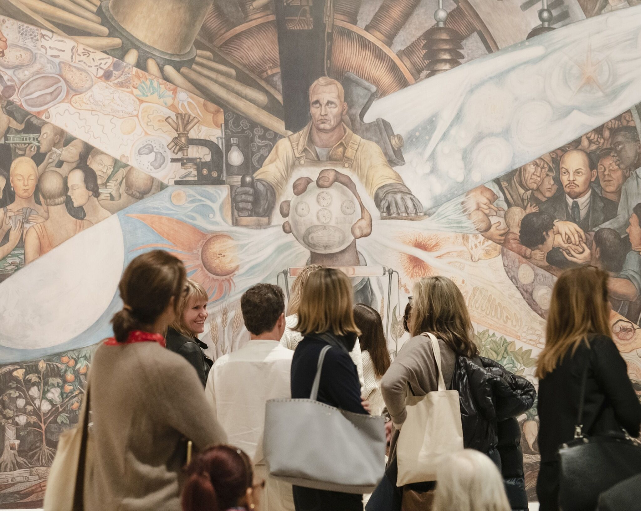 An installation photograph featuring people looking at a large mural.