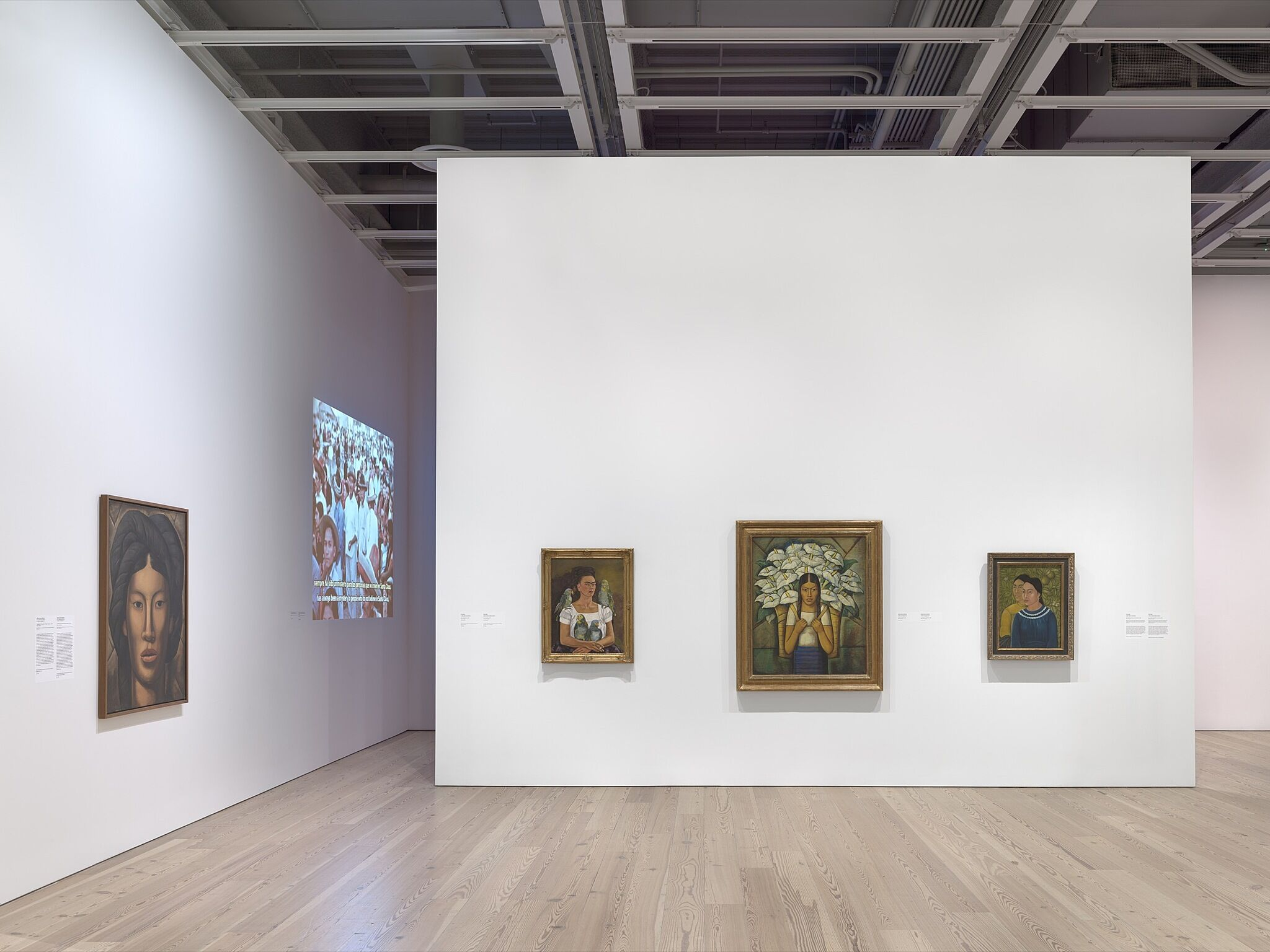 An installation photo of a gallery with paintings.