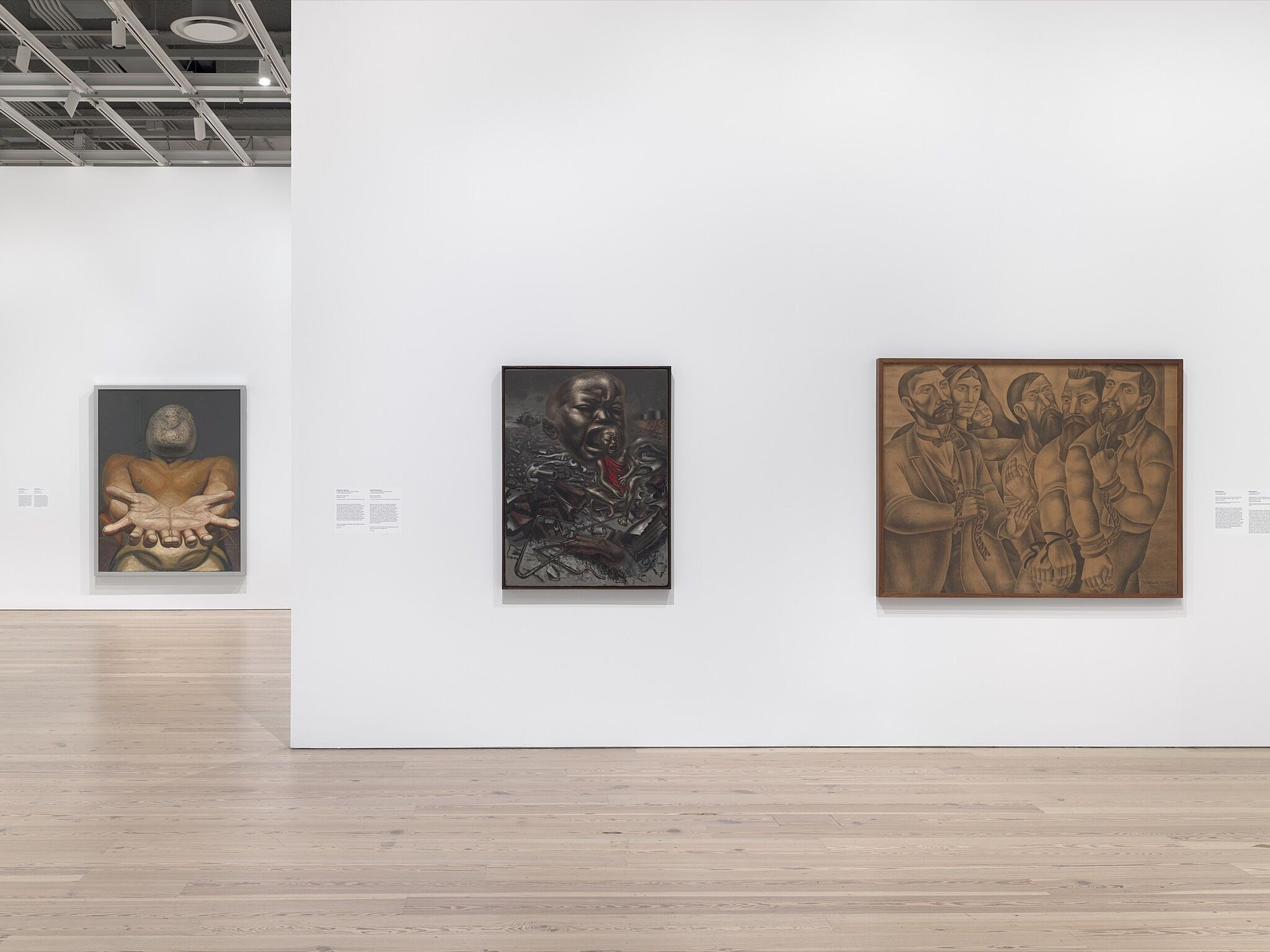 An installation photograph of a gallery with three paintings.