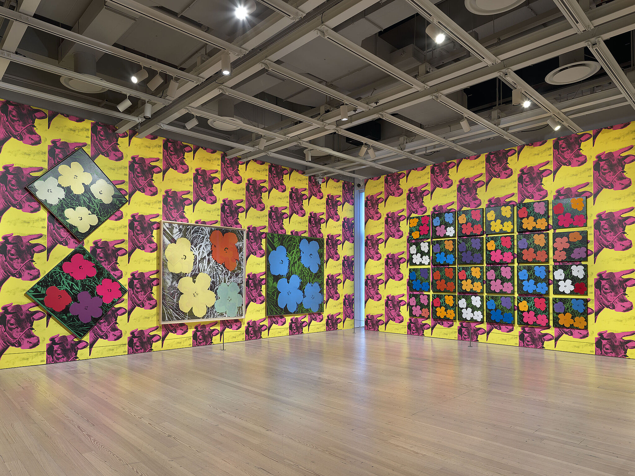 A photo of a gallery with Warhol prints filling the walls from floor to ceiling.