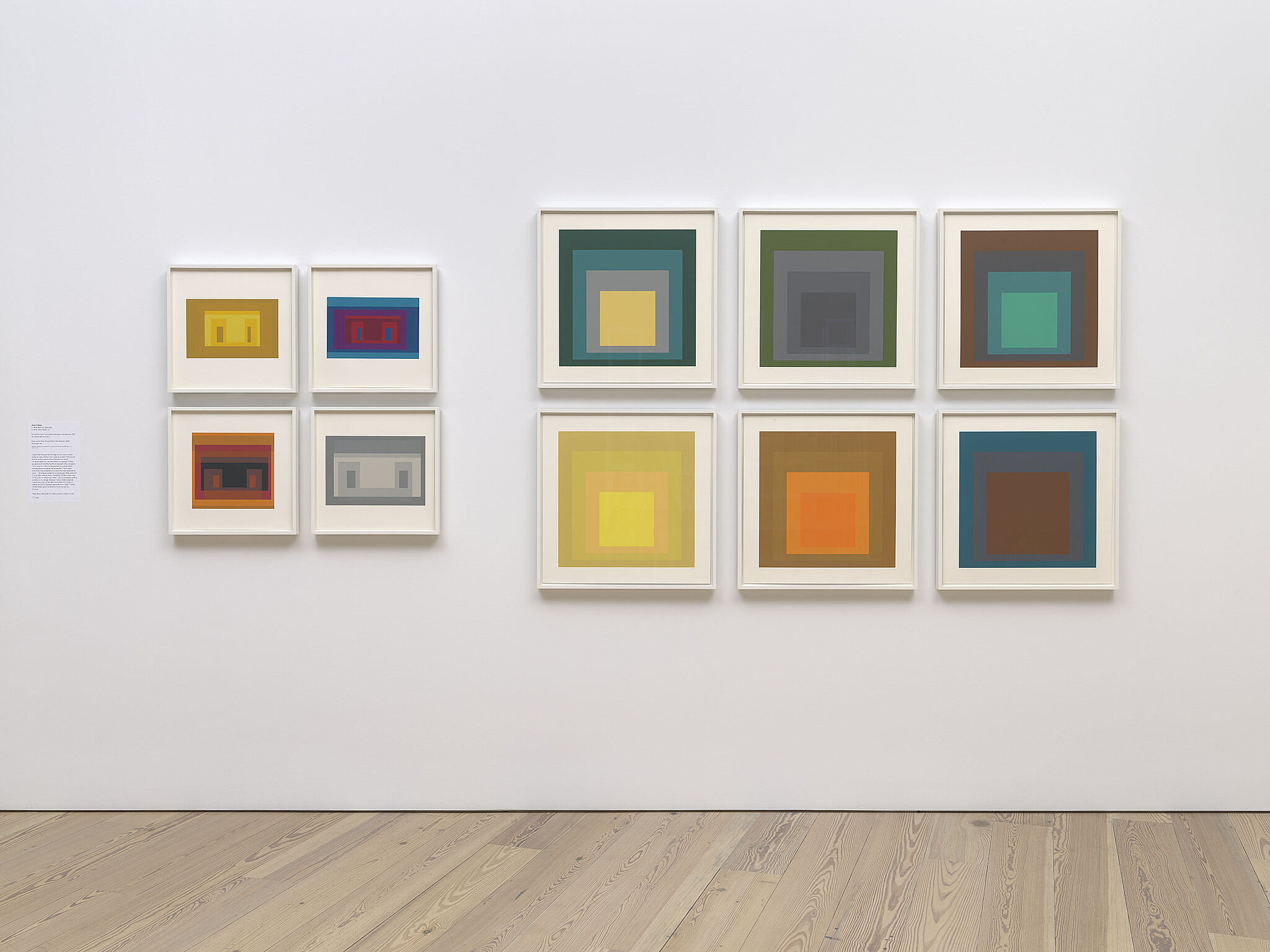 Various paintings of colored squares on a gallery wall.