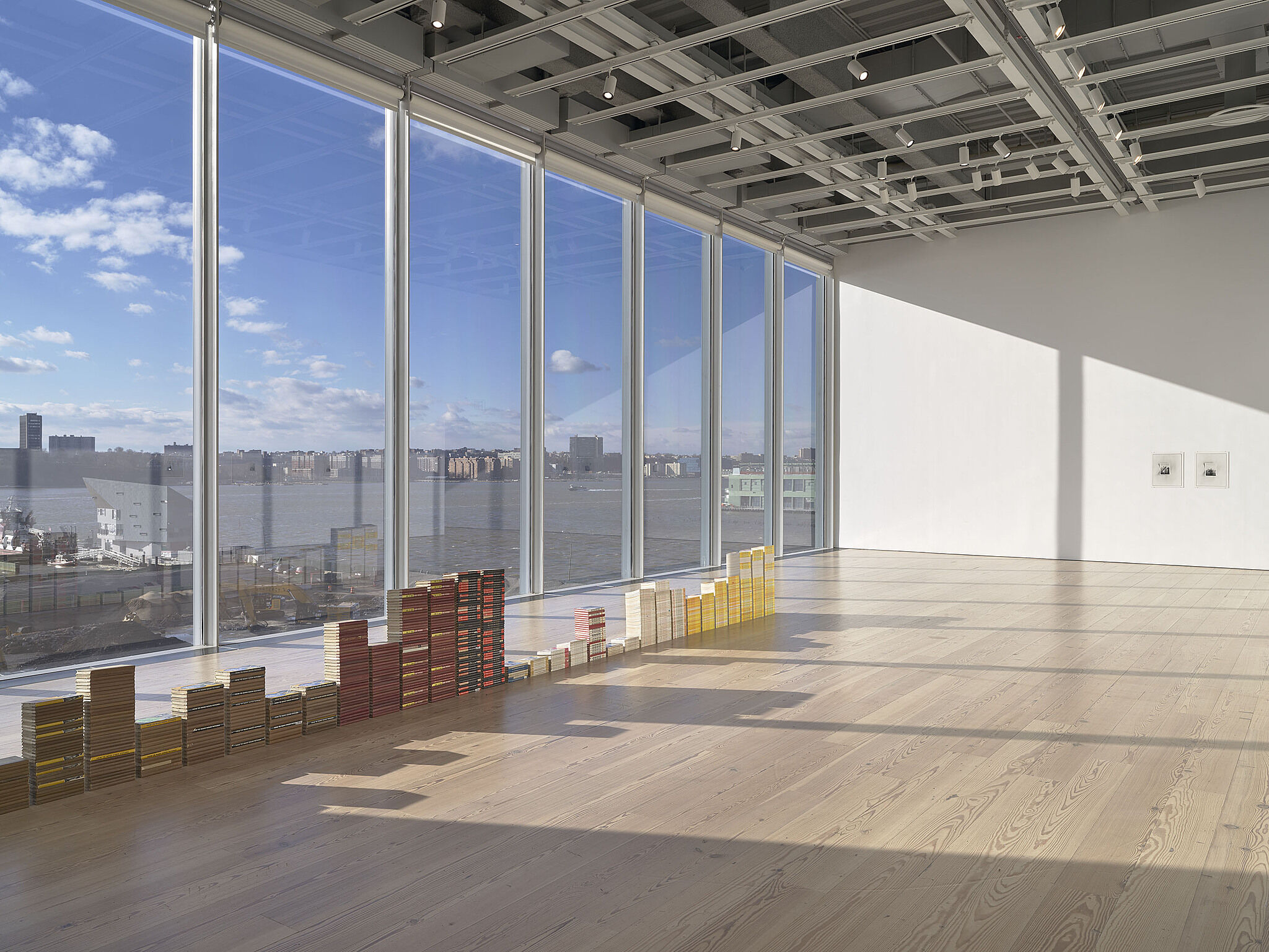 A photo of the Whitney galleries with stacks of books.